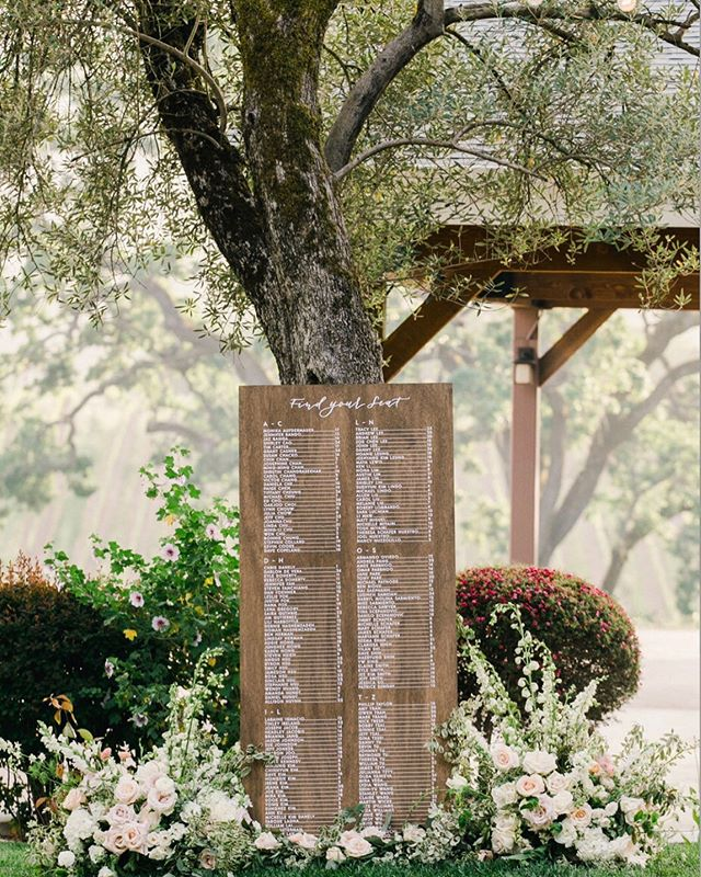 Find Your Seat || Not all plans go right. And it's okay. .. . It was roughly a month ago...at @brcohn in Glen Ellen. And the wind had just  picked up as guests were arriving for the ceremony! We had flowers at the corners and across the top of the seating chart but when one especially heavy gust of wind blew this sign by the brilliant @brownfoxcalligraphy down (not once but like twice) and our flowers landed (and dismantled) on the ground, I decided that we better move and redesign! .. . . Luckily, the planner was someone I had worked with repeatedly and had even designed her sister's wedding a few years back so I knew Michelle Chen Miyairi's style and her vision. Mostly I knew Michelle would not want the sign to be damaged and the display to look nice so moving it to a safer place would be akin to her wishes. .. . By placing it away from the open space and moving to a covered area, we found this lovely tree that served as a charming backdrop. Moving flowers from the top to the base helped as well. Floral designer Diane @tiry13dt added more flowers from the ceremony after it was over to make it a complete look. .. The value of a vendor is often found not solely by their creative work but by how they use their creativity and actions when something goes terribly wrong. .  Lastly huge thanks to the brilliant @jasmineleephoto who snapped this wonderful photo and Catering by @jessicalaskycatering who makes it look so easy. More images by Jasmine on our Instagram stories .. . #findyourseat #behindthescenes