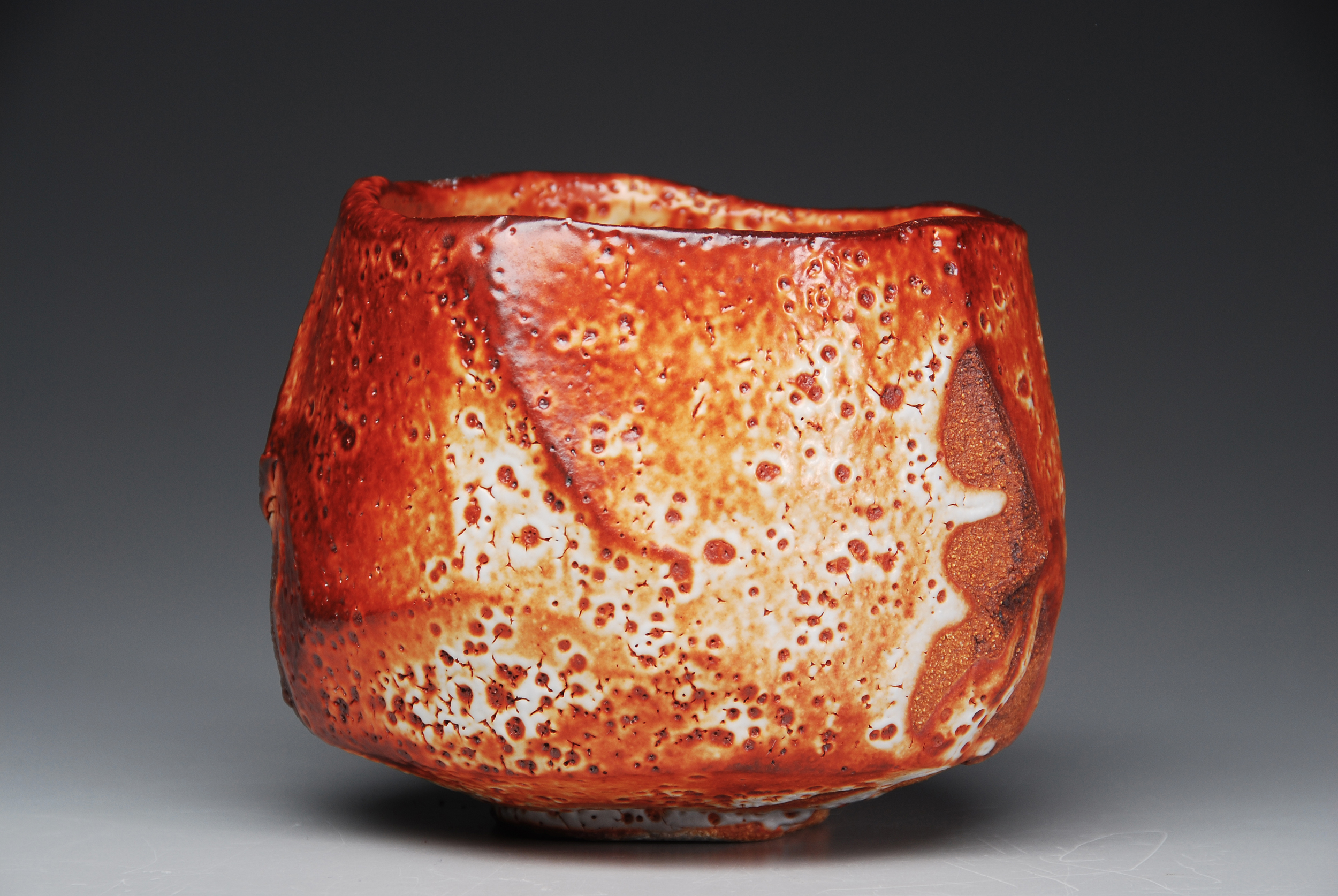 Lisa Hammond Red Shino Faceted Chawan, 2012 Crank clay thrown cut and stretched, hand cut foot with red pine knife, fired in reduction, oil fired soda atmosphere to 1300 degree 4 x 5 inches / 10.2 x 12.7 cm / LHa 1