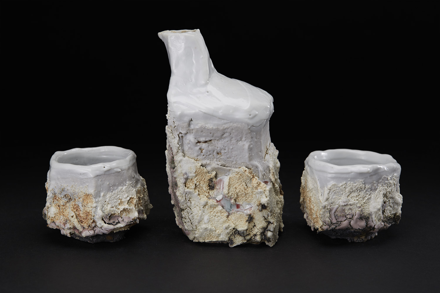 Eddie Curtis Sake set, 2016 Stoneware, reduction fired in brick built oil kiln at 1300 Celsius. Kurinuki technique, applied texture and oxides to outer surface, snow white shino to rim and inner surface ECu 14