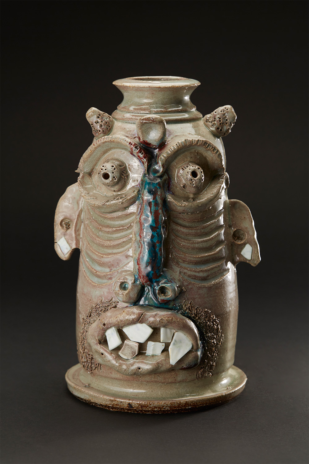 Jim McDowell    Free All People Now / My Hands Are Up Don't Shoot  , 2016 Ceramic, fired in a gas soda kiln; made of high fire clay, glazed with Malcolm Davis shino, embellished with china teeth and red and blue glass 11.5 x 7 x 7 inches 29.2 x 17.8 x 17.8 cm JMcD 9