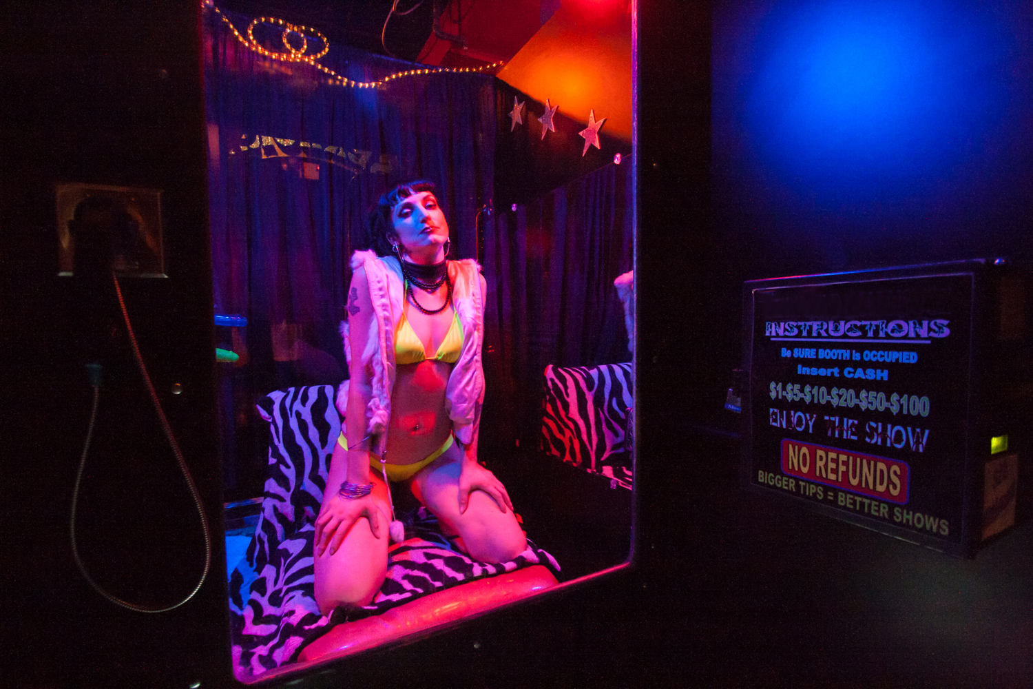 Jezebel, a live peep show performer, poses in her booth