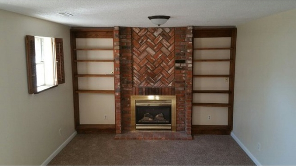 Before we moved in, the fireplace was dusty and had a brass surround. The shelves looked like an after thought and the shutters.... made me shudder.