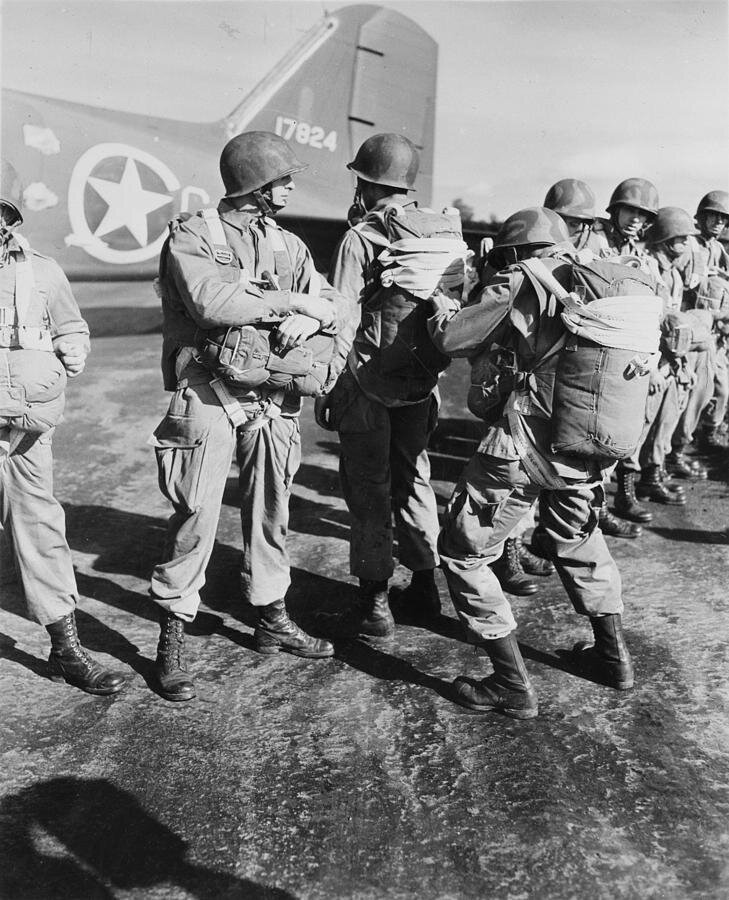 World War II, U.s. Paratroopers inspecting parachutes before taking off on maneuvers in England, circa 1942.