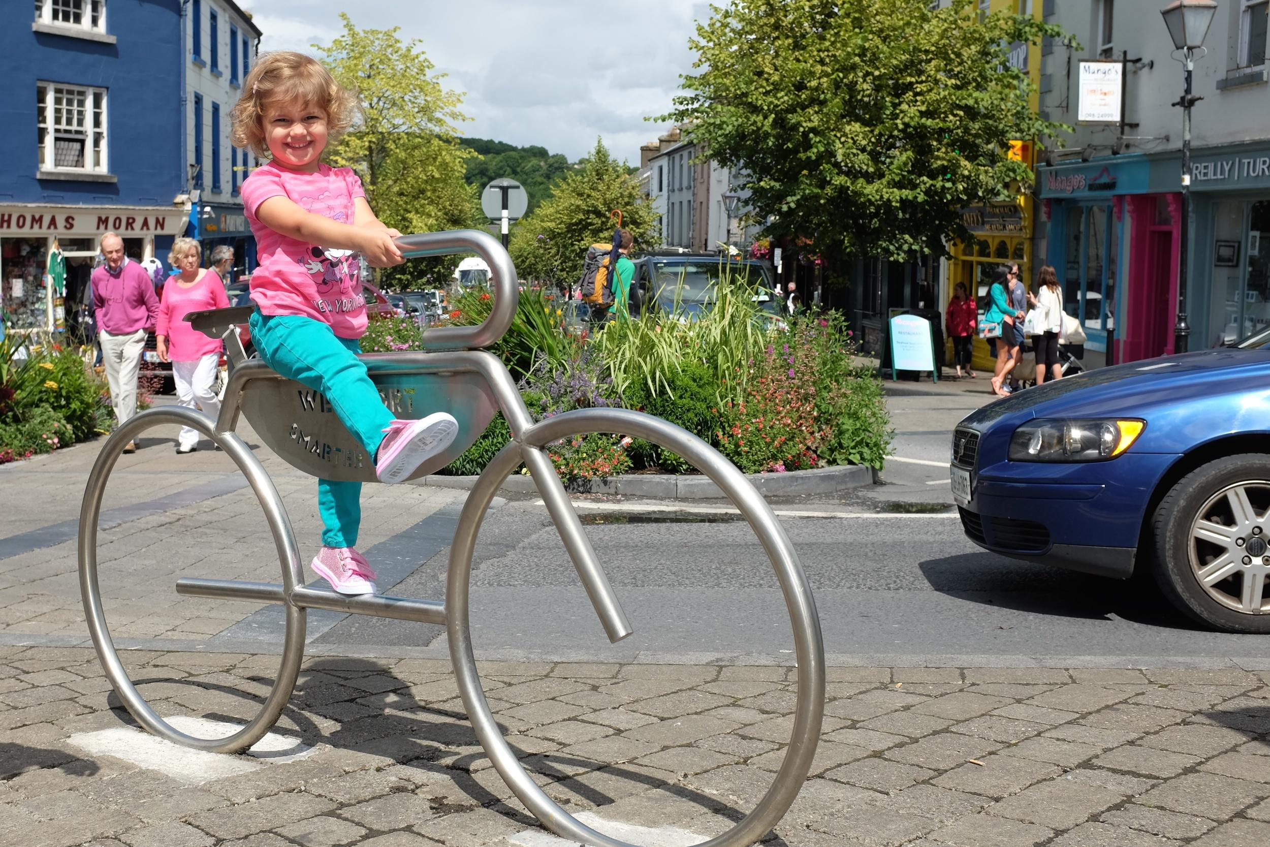"Hannah enjoying her ""ride"" on the metal bicycle"