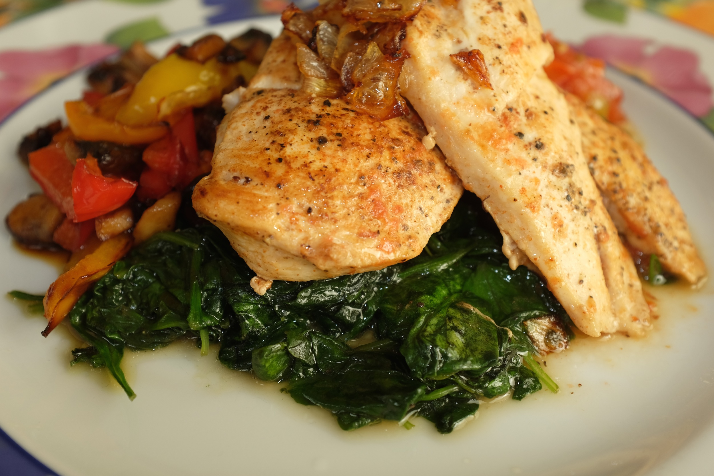 Sautéed Chicken atop Sautéed Spinach with a side of mushrooms and bell peppers