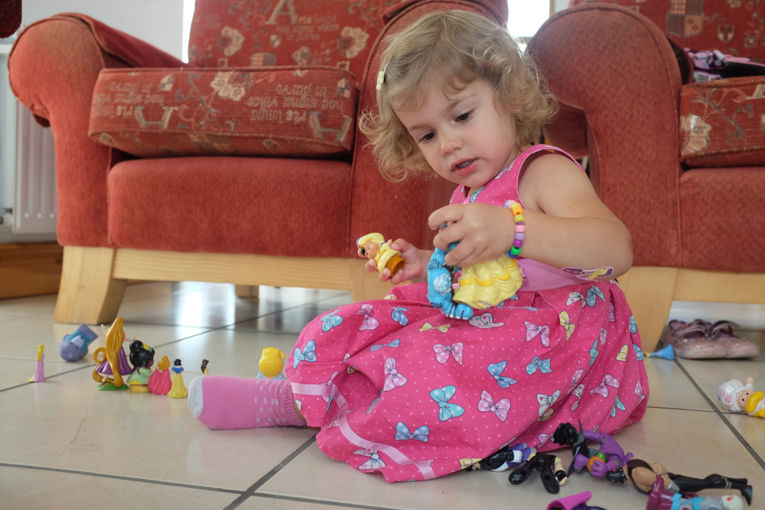 Hannah playing with her princesses and Kian's super villains