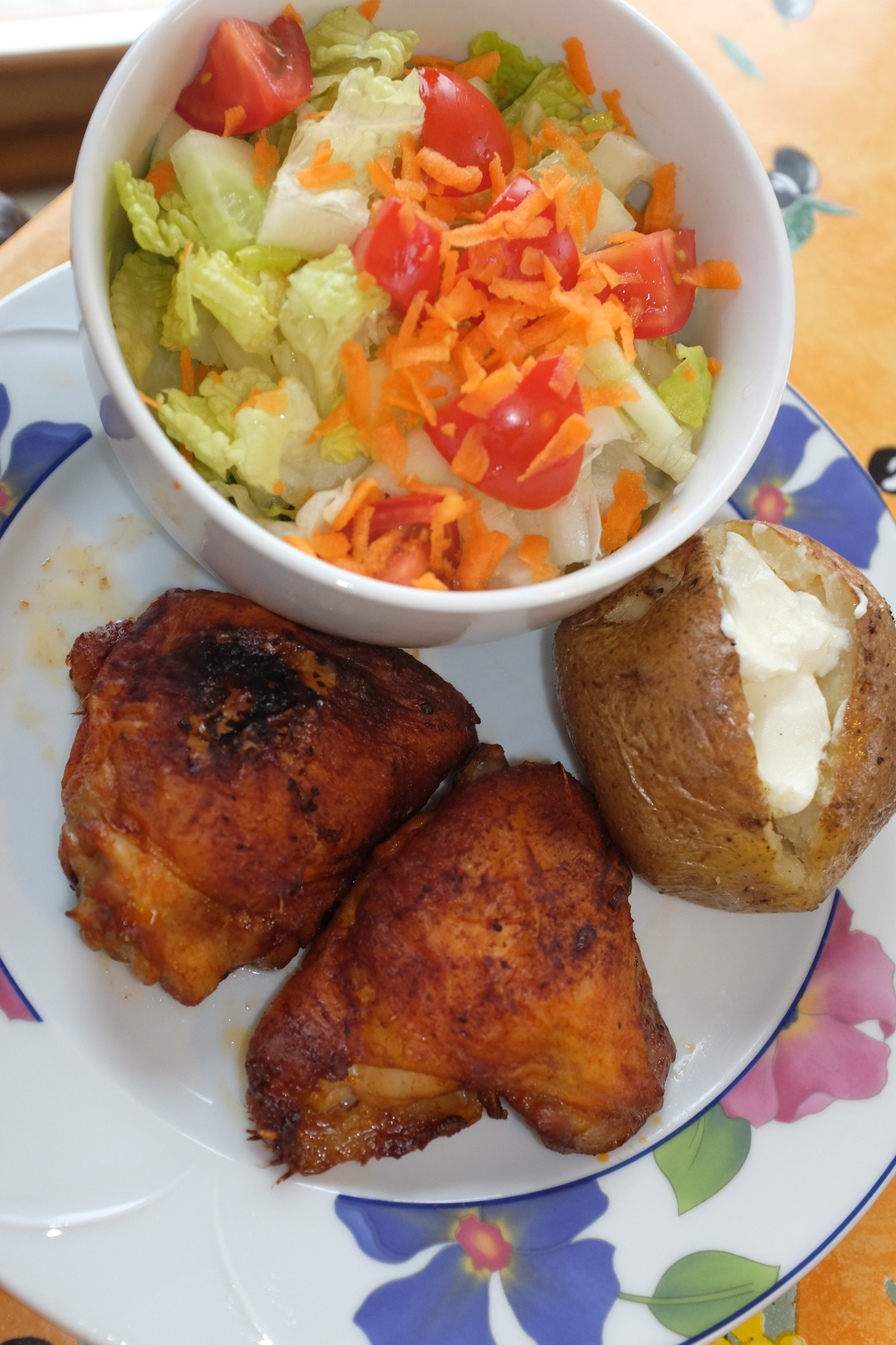 Baked marinated chicken thighs, baked potato, and a side salad