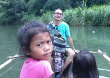 Pastor Froilan Jimenez (on the boat), secretary of LAMP in Manila, on their weekly mission trip into the forests and mountains crossing three rivers in the ministry of serving the Dumagat native people.
