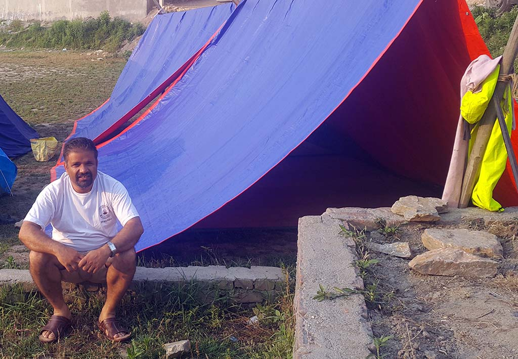 Pastor Mukunda in front of his tent
