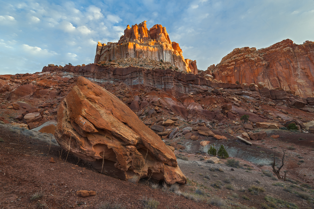 The first rays of sunlight strike a castellated formation in Capitol Reef National Park, Utah