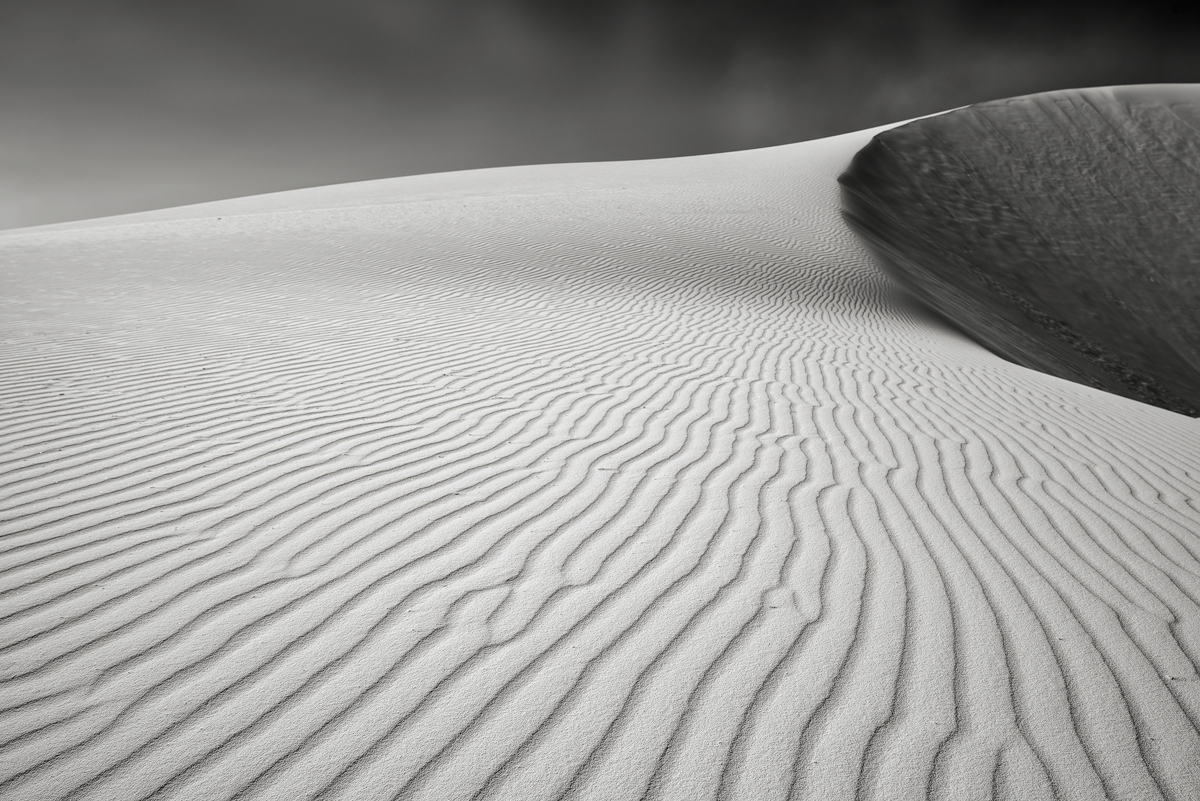 Ripples of sand lead the eye up towards the crest of a large dune.