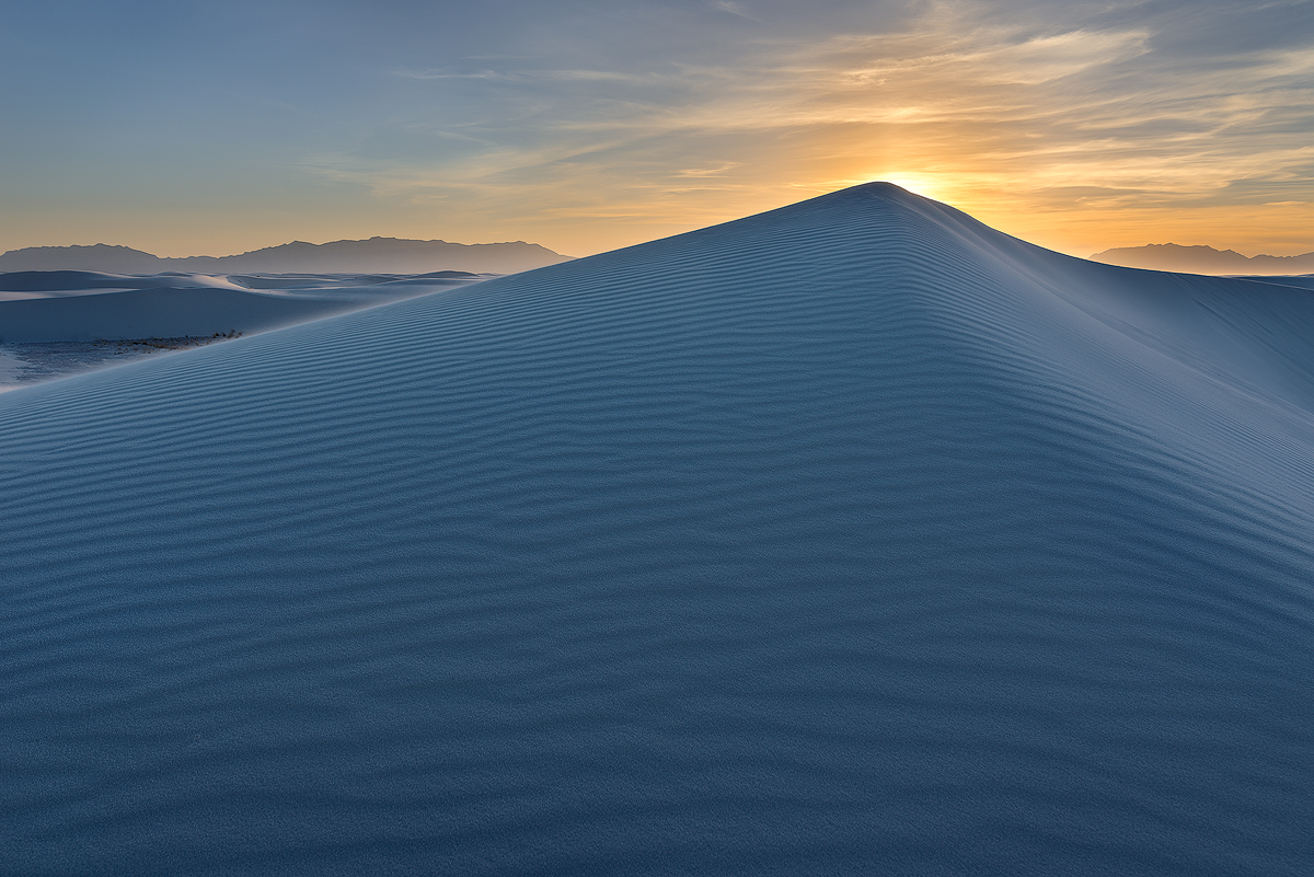 The beautiful gold tones of sunset offset the blue light and shadows of a pyramidal sand dune.