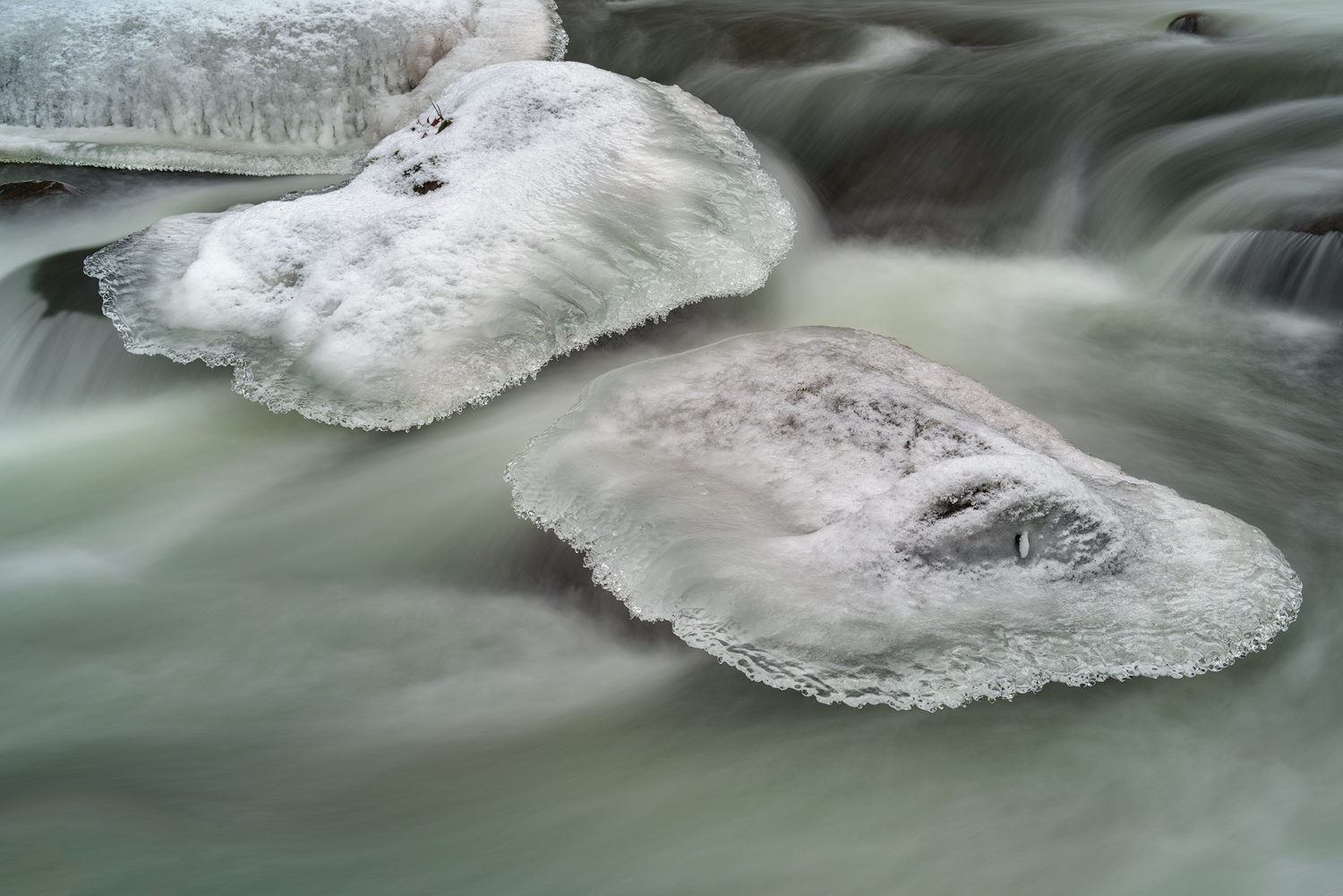 Winter ice forms over top of rocks within the icy flow.