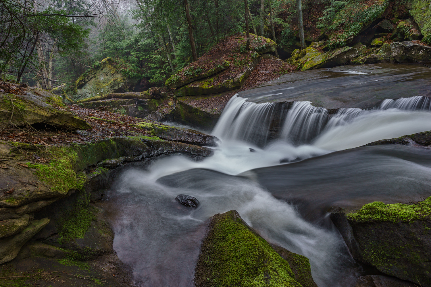 The sweeping forms of the rocks force the creek into a narrow slot and over a hanging sandstone shelf. Shot with a Sony a7II and a Zeiss Loxia 21mm, f2.8. Image exposed at ISO 50, at f11 for 3.0 seconds.