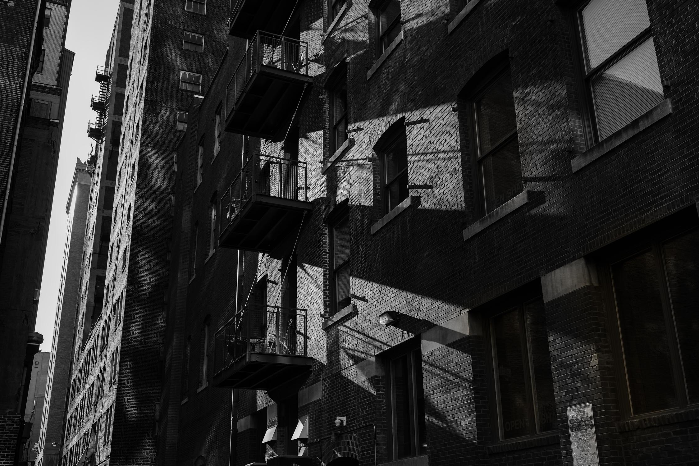 Sunlight through an open slot casts shadows on a brick facade. Fuji X-Pro 2 and a Fujinon 16-55mm f2.8.