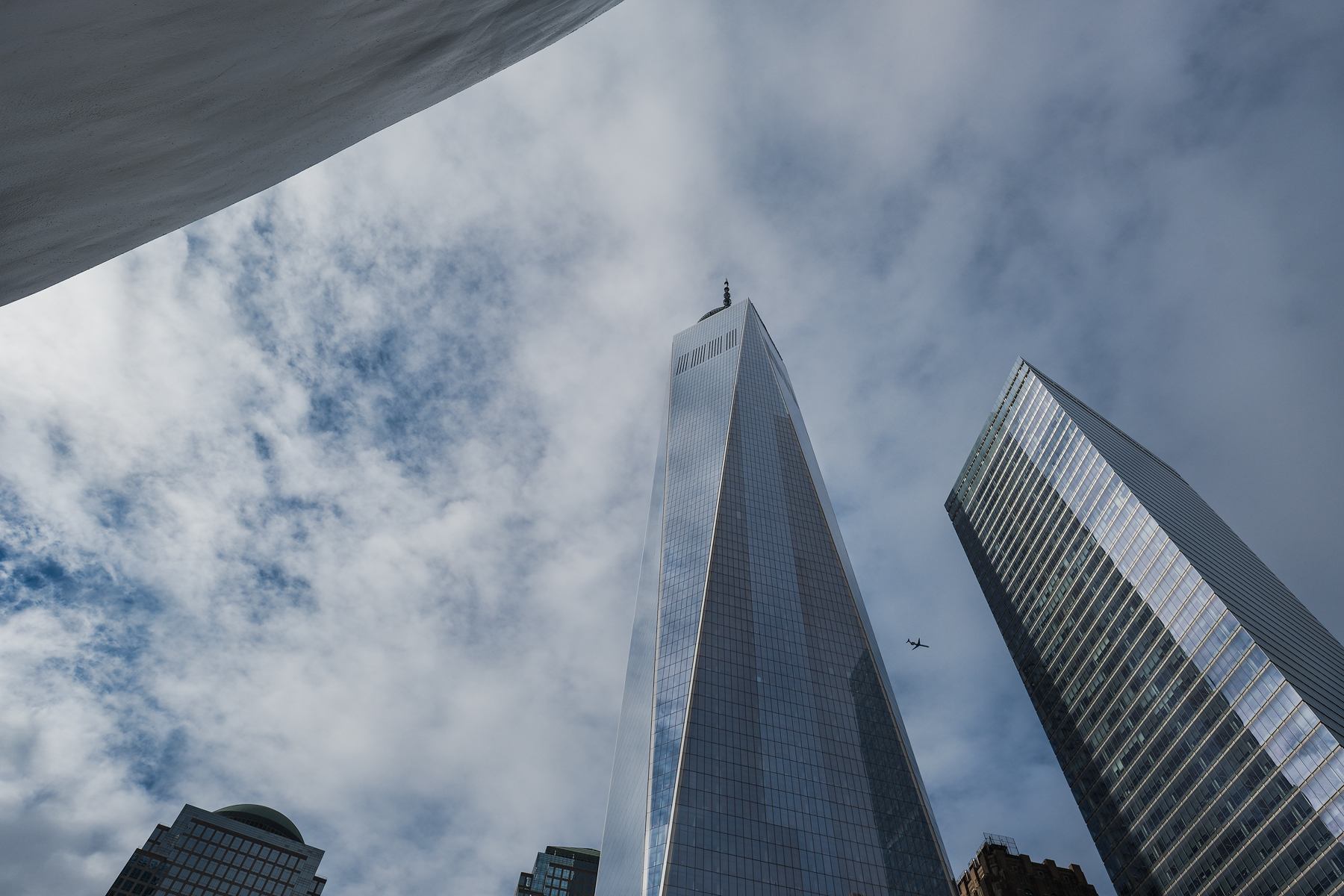 High, and far away, a plane appears between The World Trade Center and another tower.
