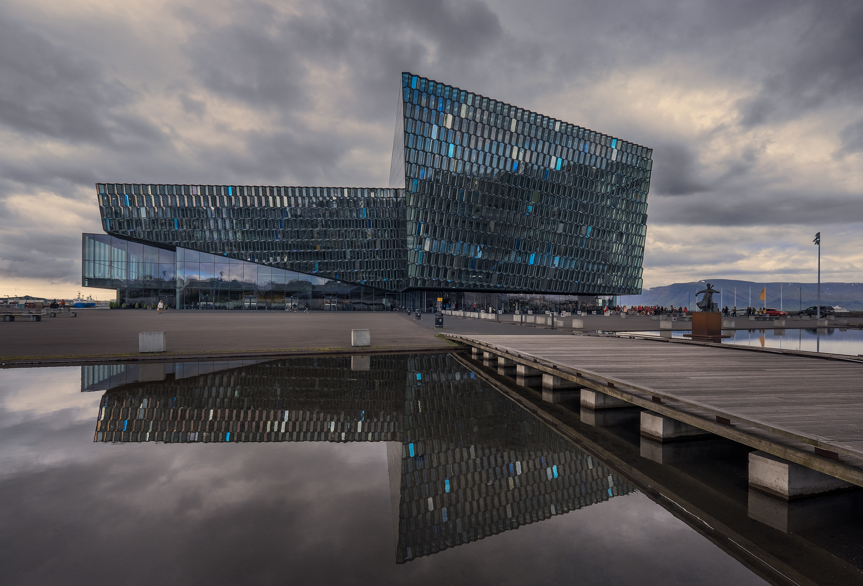 In this image the building reflects the somber blue tones of the late evening and cloudy sky.