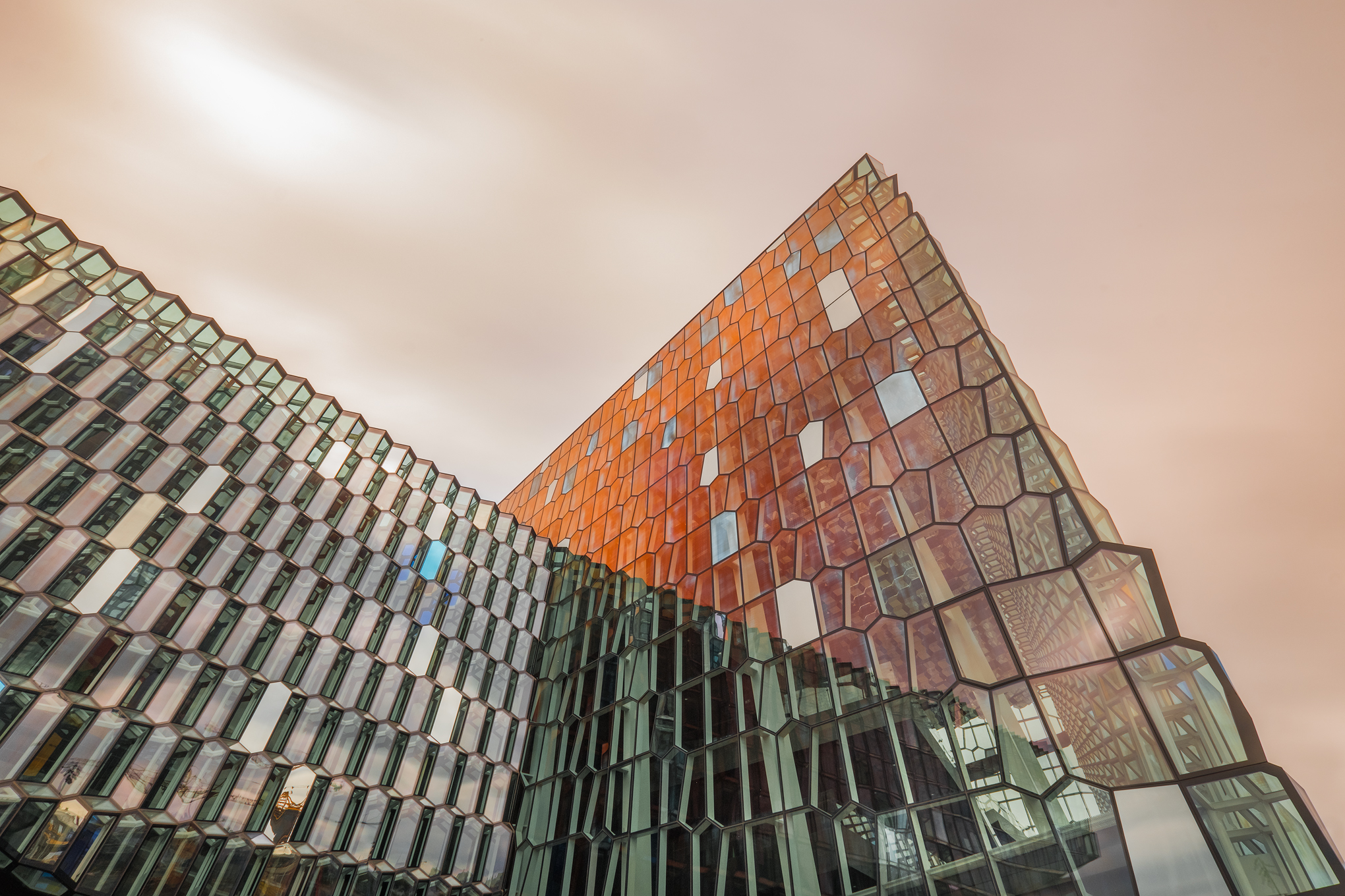 The Harpa glows red from reflected sunset light.