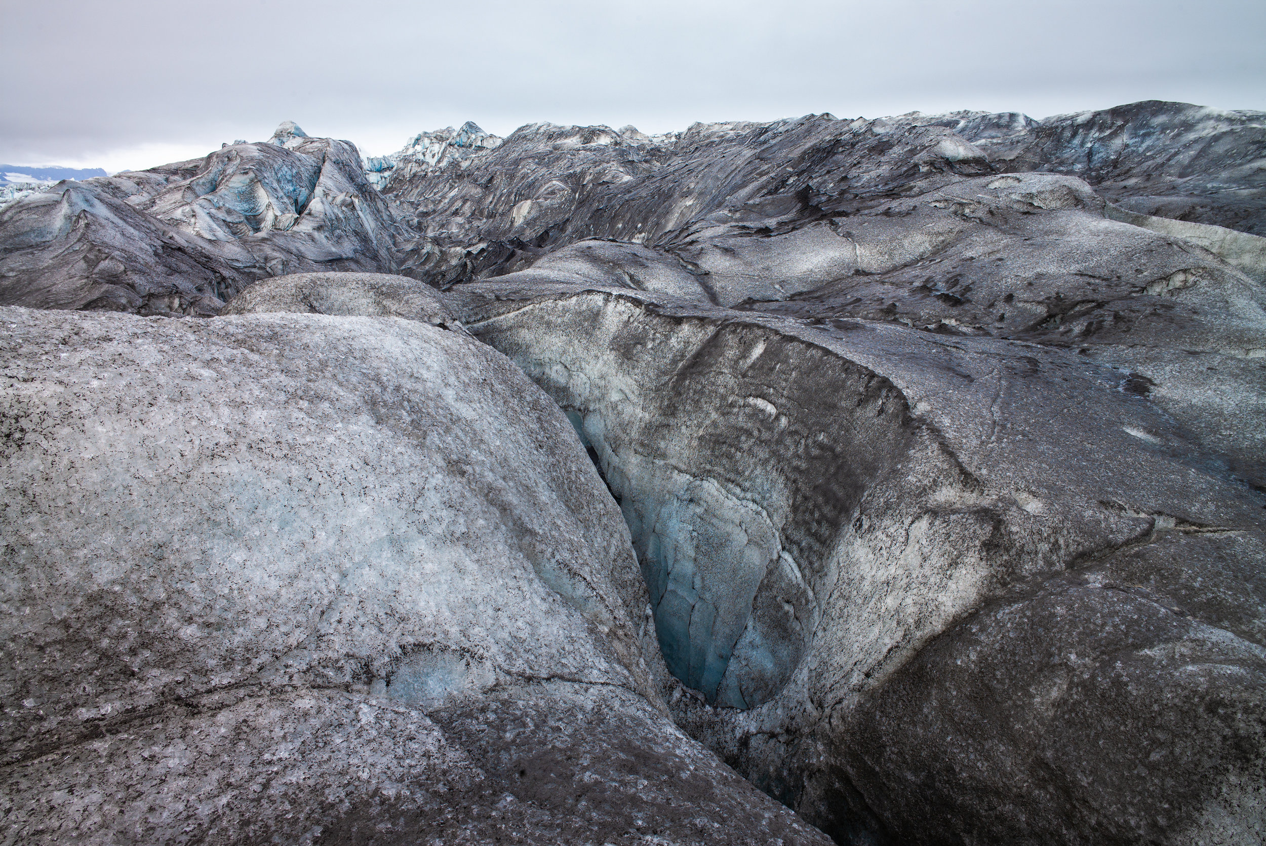 Undulating ice forms into ridges, valleys, and deep wells leading into the glacier.