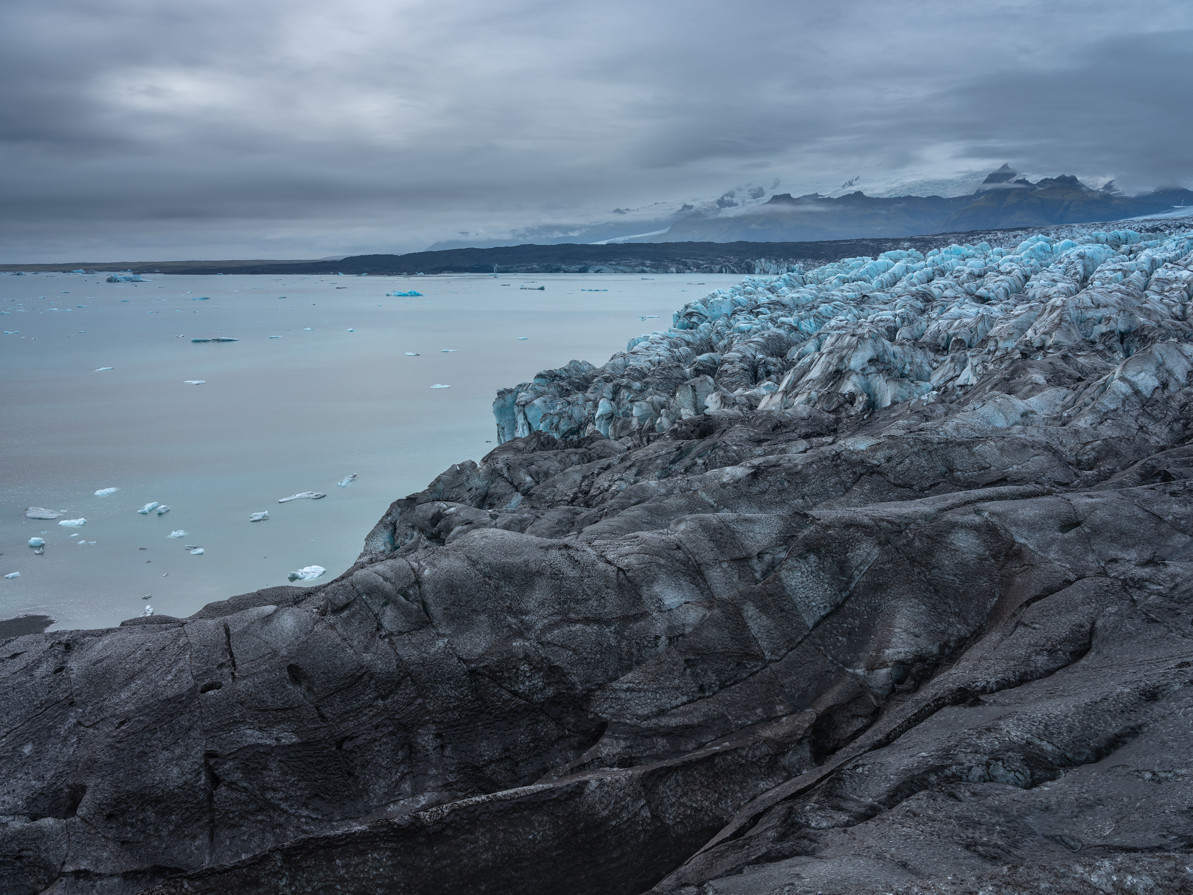 Black ridges of ice give way to the ice seracs that feed the glacial lagoon.