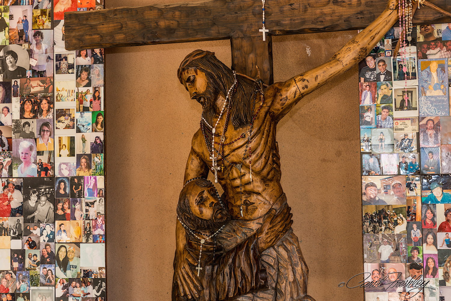 Statue in new open porch. Photos of loved ones are left on the walls with requests for prayers.