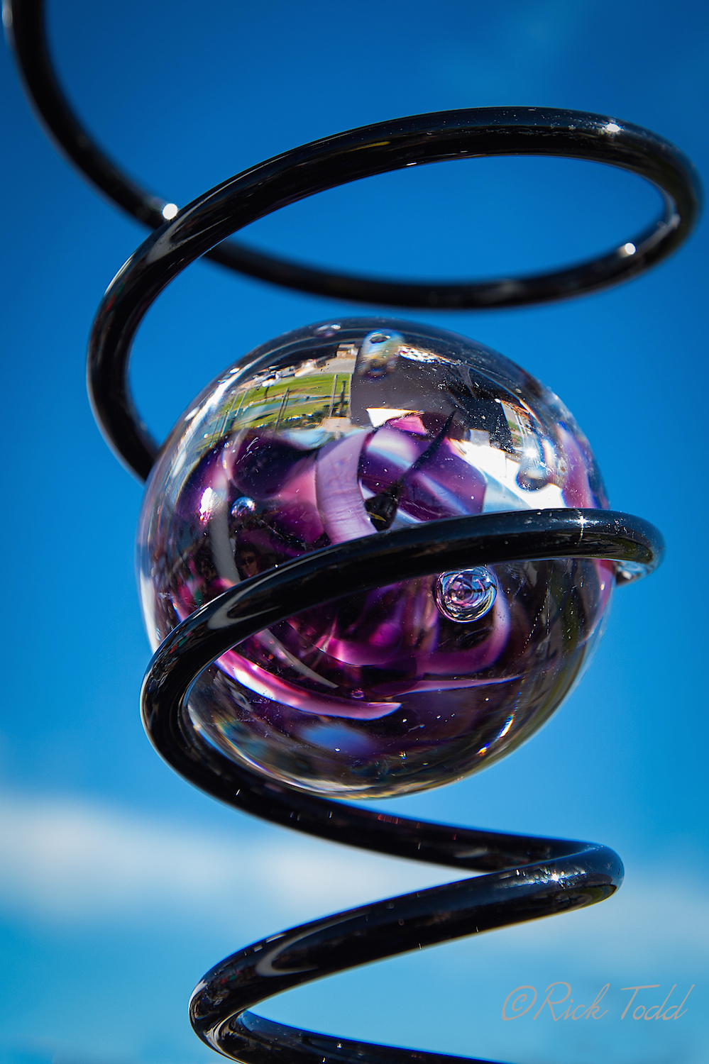 The glass blown ball is placed inside the spiral wire which is twisted by the wind.  An optical illusion is created suggesting that the ball moves and spins up and down the spiral.  Very cool.  I notice that Rick caught the reflection of the lake in the ball.  Good job!