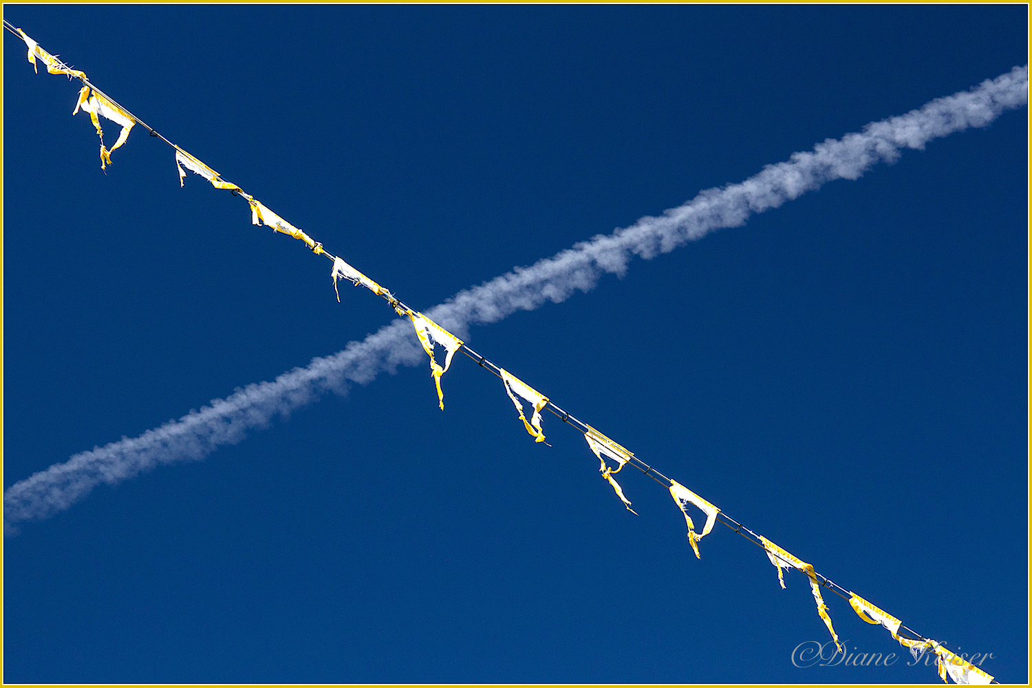 Diane captured a symbolic cross over of prayer flags and jet trail.