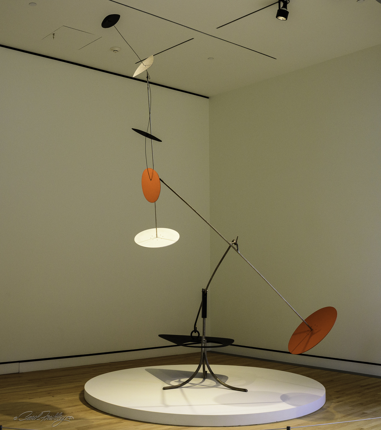 This mobile by Alexander Calder (1898-1976) is a classic example of Calder's standing mobiles.  Made of painted sheet metal,  Trois noirs sur un rouge (Three Blacks over Red) , 1968, achieves graceful balance in motion.  Calder, ''challenged the traditional definition of sculpture as three-dimensional mass, creating works of art made from metal rods and biomorphic sheet metal planes that move with the air in varied and spontaneous paths.""
