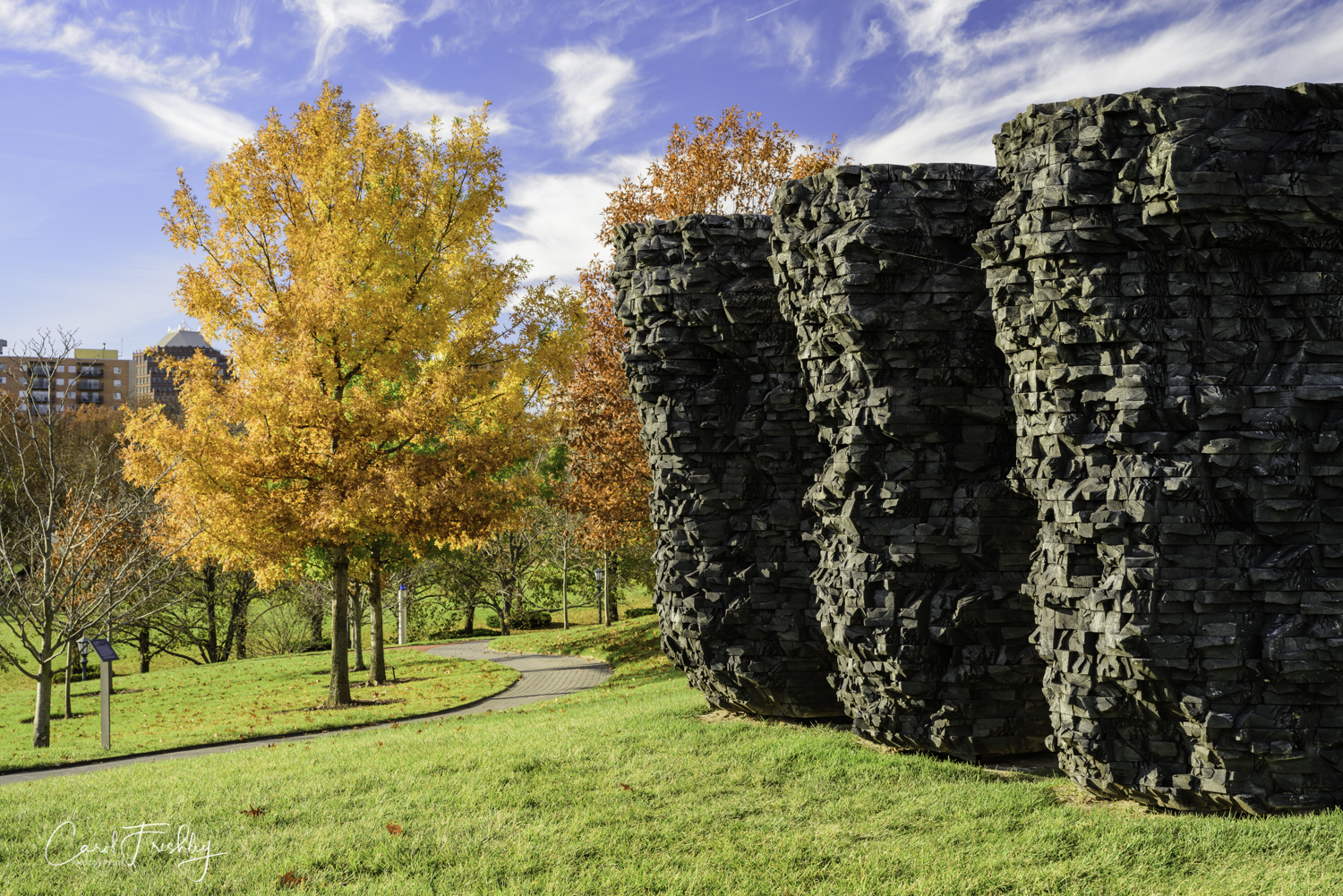 """Ursula von Rydingsvard (American of Polish descent, born 1942) sculpts intuitively and without drawings or models to guide her process.  She creates each sculpture directly from a mental image that evolves as she works.  The roughly hewn, steeply vertical surfaces of  Three Bowls  bring to mind weathered, rocky cliffs.  Von Rydingsvard reinforces this impression by saturating the wood with black graphite, which silvers as it ages.  The artist stated, ""I am drawn tot hat part of the world where man-made walls erode in a way where there is no longer a strict line between that which man has made and that which nature has made.""  Made of cedar and graphite in 1990."