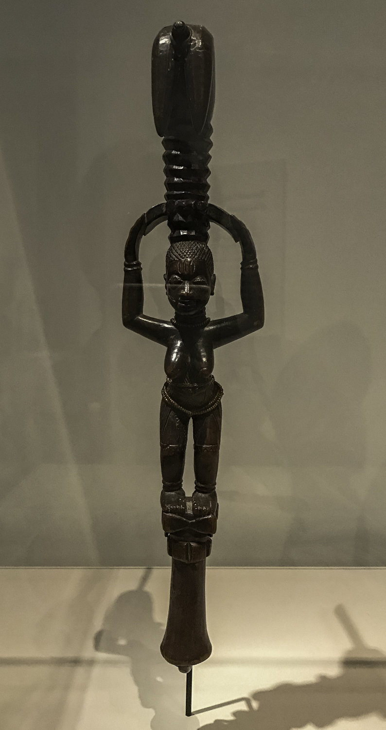 "Shango Staff,   Benin, Yoruba culture, Wood, glass bead, brass, iron and plant fiber, 1900s. ""Carved from a single piece of wood, the sensuous, staked forms of this Yoruba staff create a dynamic play of three dimensionality and negative and positive spaces."""