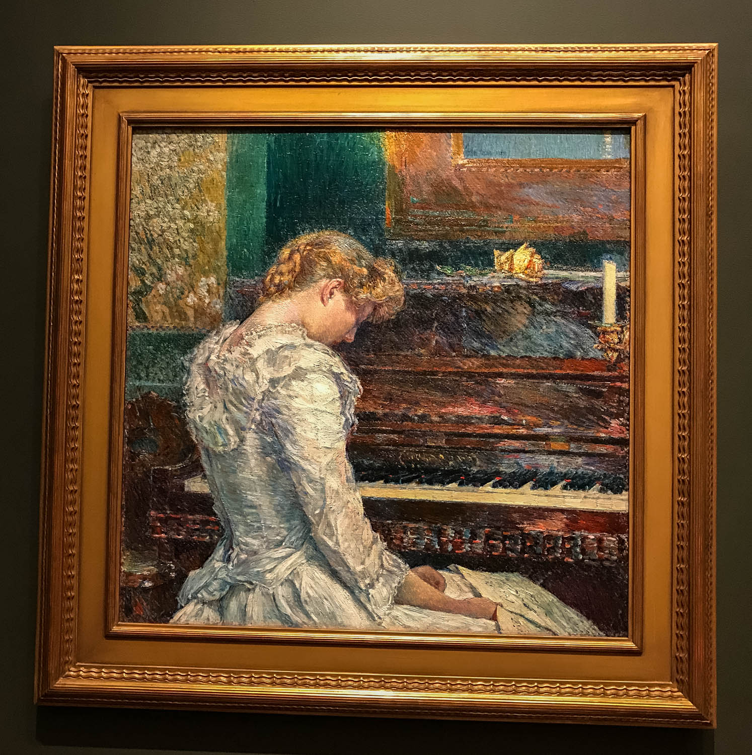 """The Sonata , 1893 by the American Childe Hassam (1859-1935), oil on canvas. From the tag: """"Combining luminous color, staccato brushwork and academic drawing, Childe Hassam's  The Sonata exalts sensory and aesthetic experiences. The painting feature a pianist having just performed Beethoven's famously difficult  Sonata Appassionata, a score for which she holds in her lap. He slouched posture, echoed by a similarly beautiful but fragile looking yellow rose atop the piano. A Japanese scroll showing a blossoming cherry tree also evokes the dual pleasures of sight and smell."""" The piece demonstrates the artist's endorsement of a late-19th century movement that proclaimed that art was not obliged to tell a story or to impart morals. Instead, art could be viewed as uplifting society by celebrating beauty."""