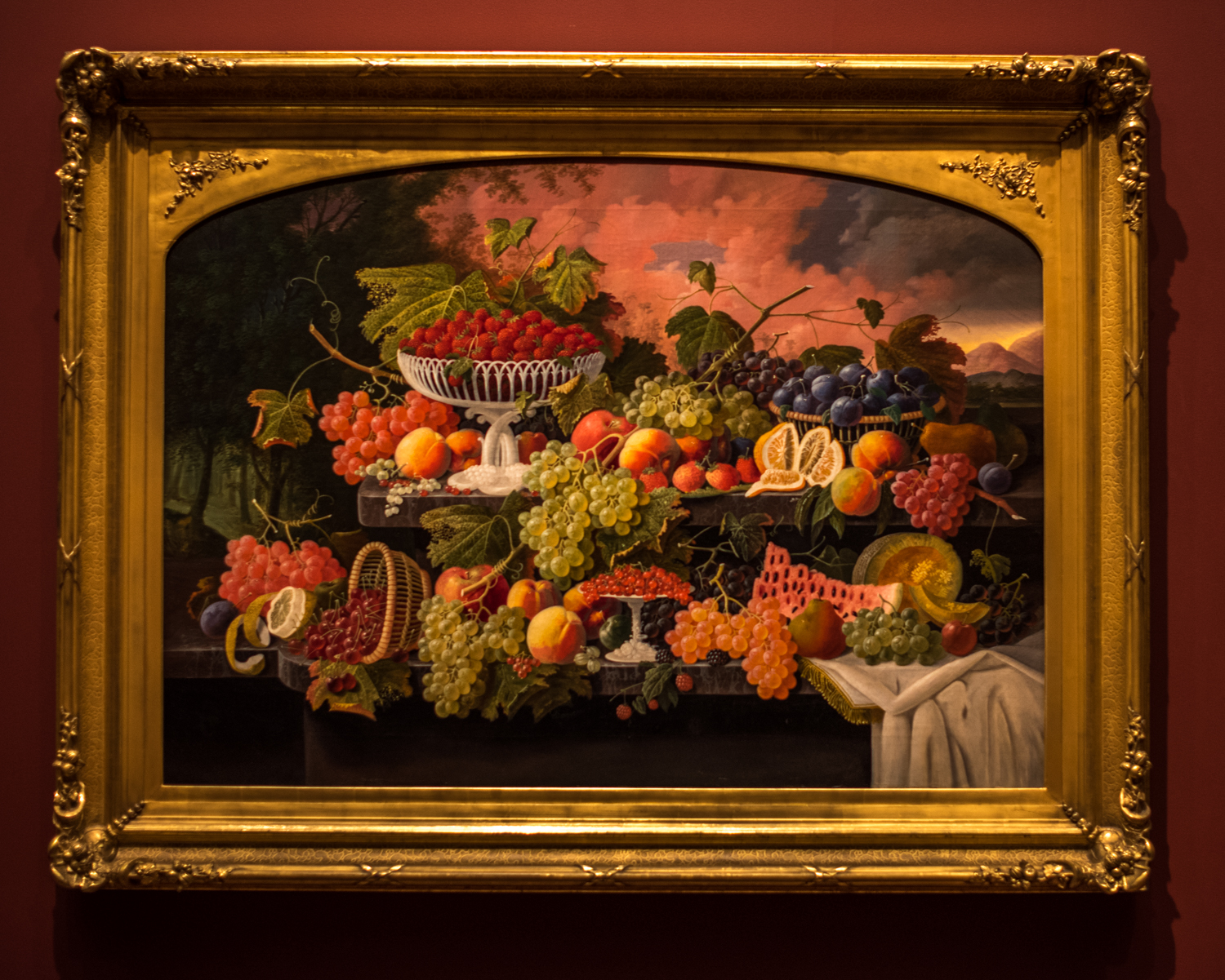 """Two-Tiered Still Life with Fruit and Sunset Landscape 1867 , Severin Roesen (1815-1872), oil on canvas. From the information tag: """"Severin Roesen's bountiful still life celebrates and reinforces the popular 19th century notion that America's natural resources distinguished the nation from the rest of the world. In majestic proportions and a vivid palette, an abundant variety of fruit sits atop a two-tiered marble shelf. The dense forest at left and the mountain landscape at right suggest the diversity and power of the American landscape. Painted around the time of the Civil War, the canvas' dramatic and somewhat threatening sky may suggest the question of whether or not America's unique democracy would prevail."""""""