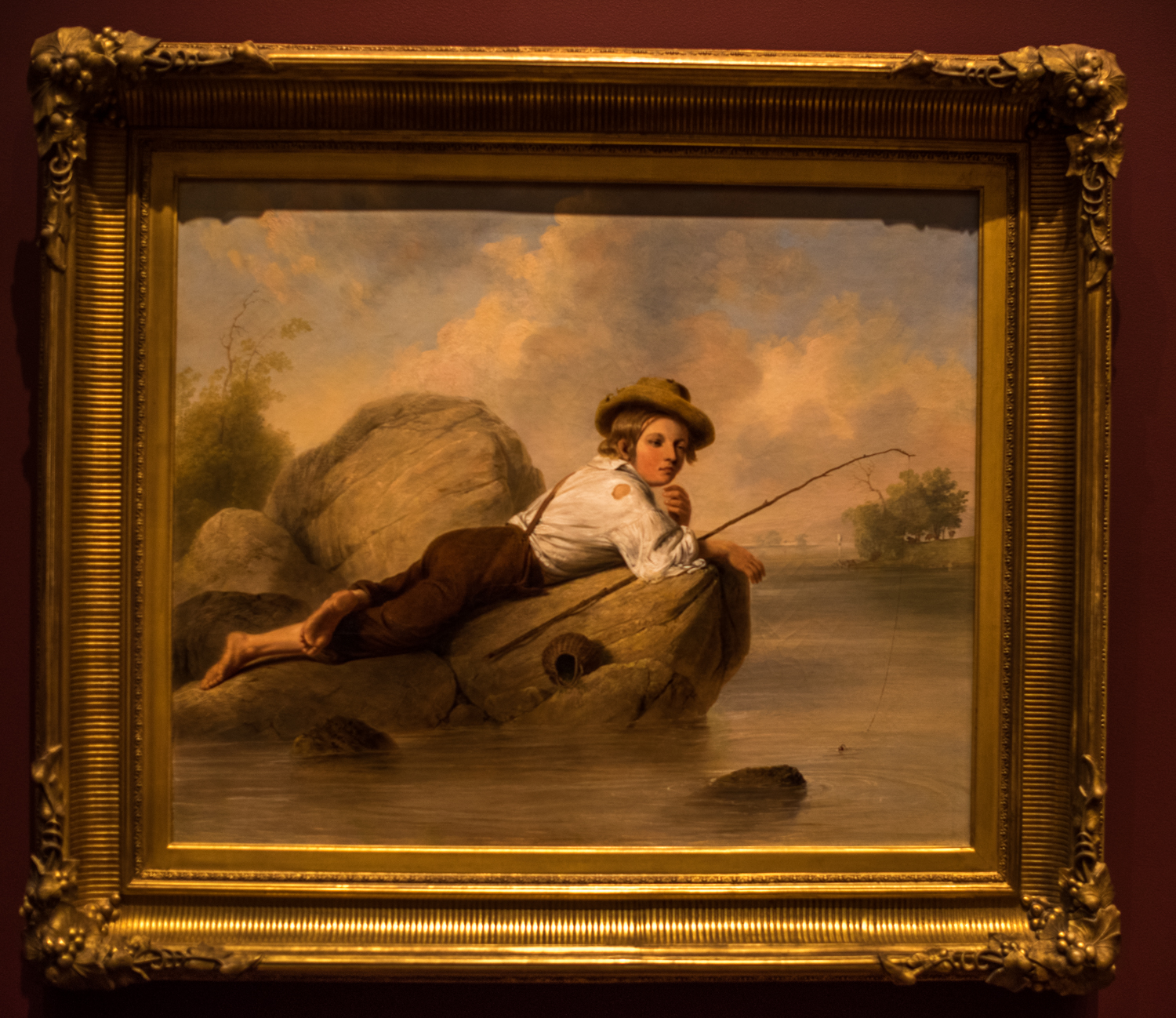 """A Lazy Fisherman , 1844 by John Gadsby Chapman, (1808-1889, oil on canvas. From the information tag: """"A critic in 1844 described this barefoot boy in ragtag clothing as """"laziness personified"""". His complete ease is embodied in his languid pose and heavy lidded eyes and echoed in the fallen basket, lax fishing line and sluggish river. This sentimental view, rendered with creamy, smooth brushwork, developed from John Gadsby Chapman's experience illustrating volumes of romantic verse. His talent for drawing is revealed in the boy's hat, clothing and especially in the out-turned foot. . . . Pleasing scenes of children were especially popular in the mid-19th century as they offered musings on childhood innocence and freedom in an increasingly challenging world."""""""