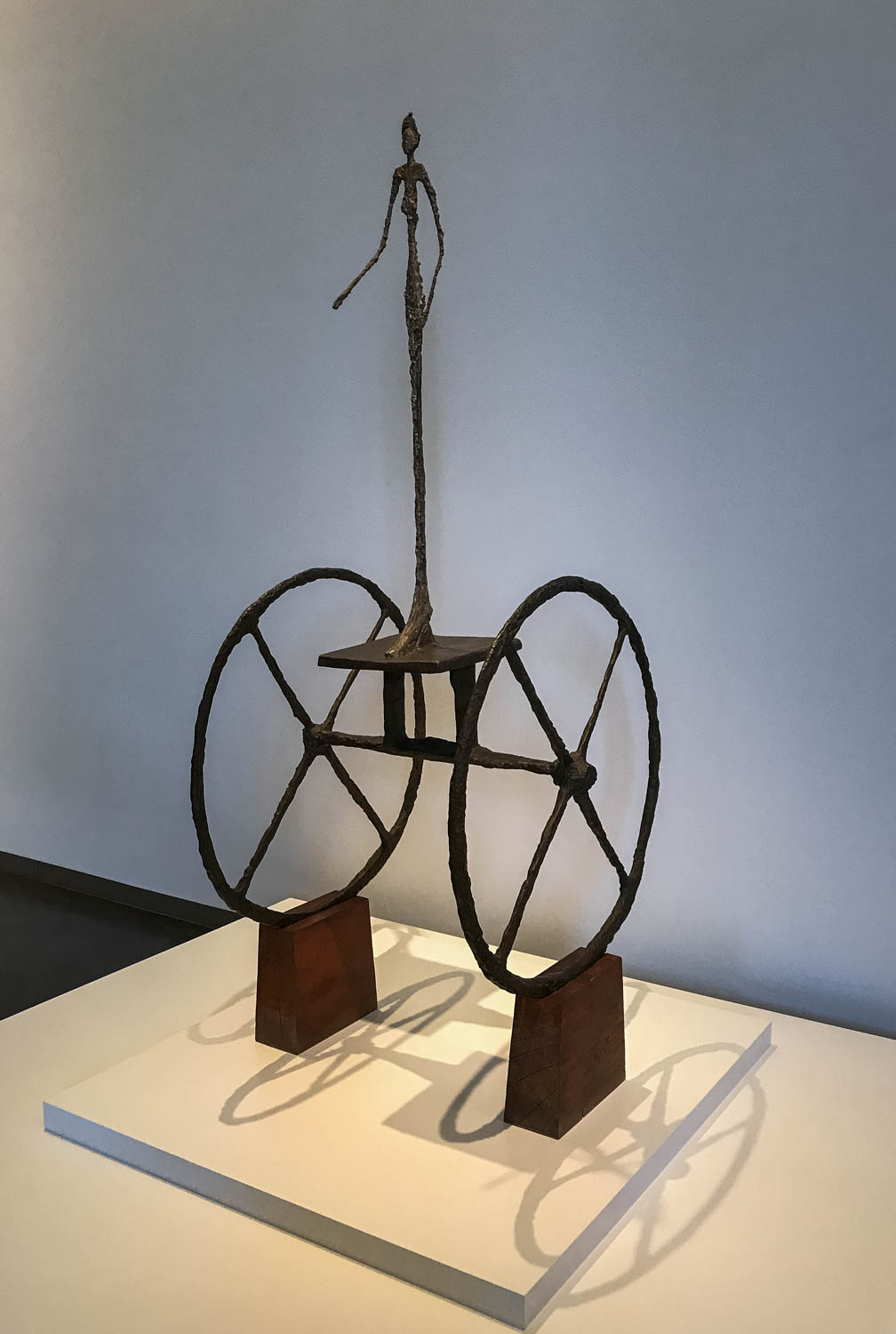 """The Chariot , 1950 by Alberto Giacometti (1901-1966) painted bronze. """"The solitary, emaciated figure in  The Chariot , frozen in a precarious stance, is a poignant reminder of the fragility of life. The sculpture is associated with Etruscan and Egyptian chariot motifs as well as with Giacometti's memories of 'a pharmacy wagon being wheeled around the room' in the Bichat Clinic where he was a patient during World War II. Equally significant to  The Chariot is he existential philosophy of his friend Jean-Paul Sartre. Existentialism emphasizes the isolation of the individual in an indifferent universe, where existence is defined by an individual's choices."""""""