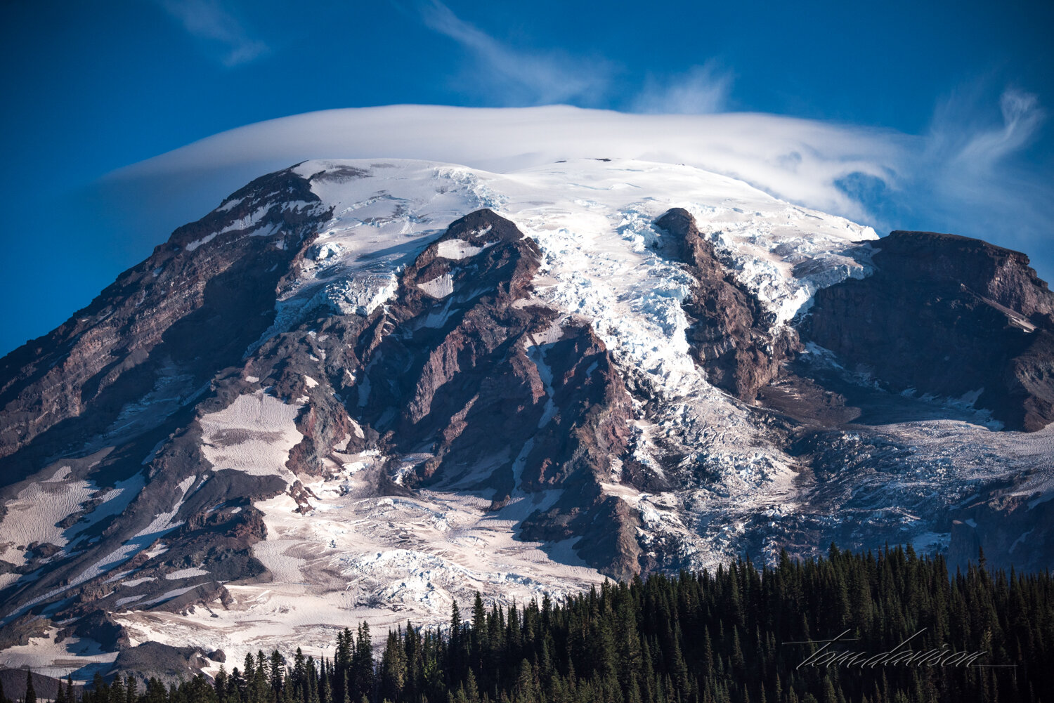 Mountains as large as Mt. Rainier can produce their own weather systems. Seeing a cap on Mt. Rainier was not unusual.