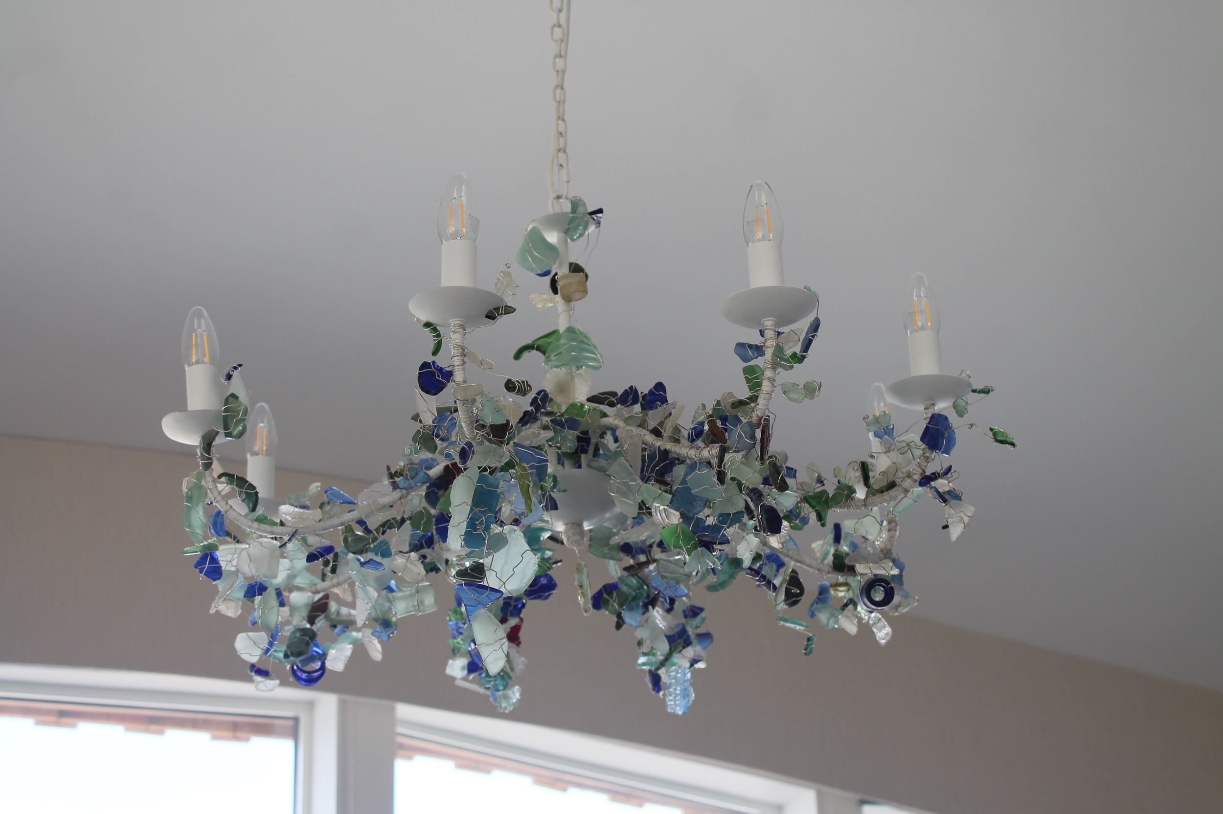 This special feature chandelier was made by Jane Blanchard, our interior design partner, from many pieces of seaglass painstakingly wired in place