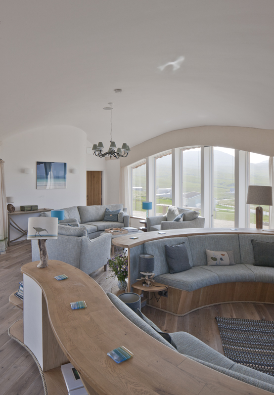 The lounge area, as well as the whole house, has superb views to the beaches, ocean, islands and sunsets.  The blinds on the huge windows were carefully designed to be completely hidden when not in use, and the Smart TV rises on a lift so it doesn't interrupt the incredible views in the daytime