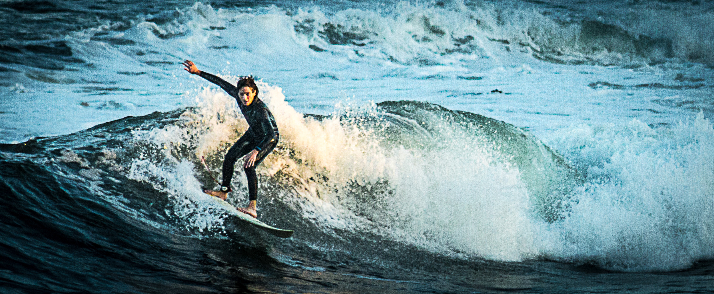 A surfer finds a righteous wave with a heavenly glow during a recent swell in Narragansett, R.I.