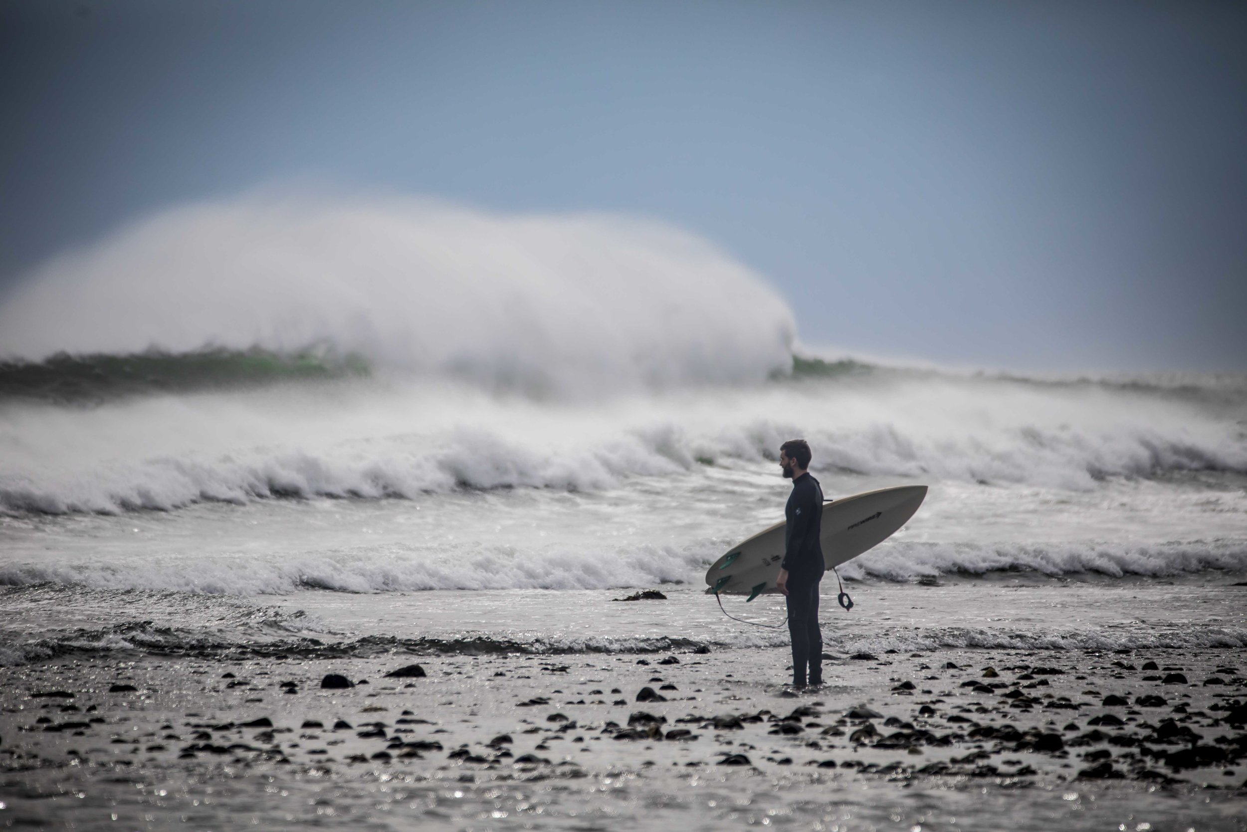 A surfer sizes up the massive swells before heading into the lineup during a September surge at Deep Hole in Matunuck, R.I.