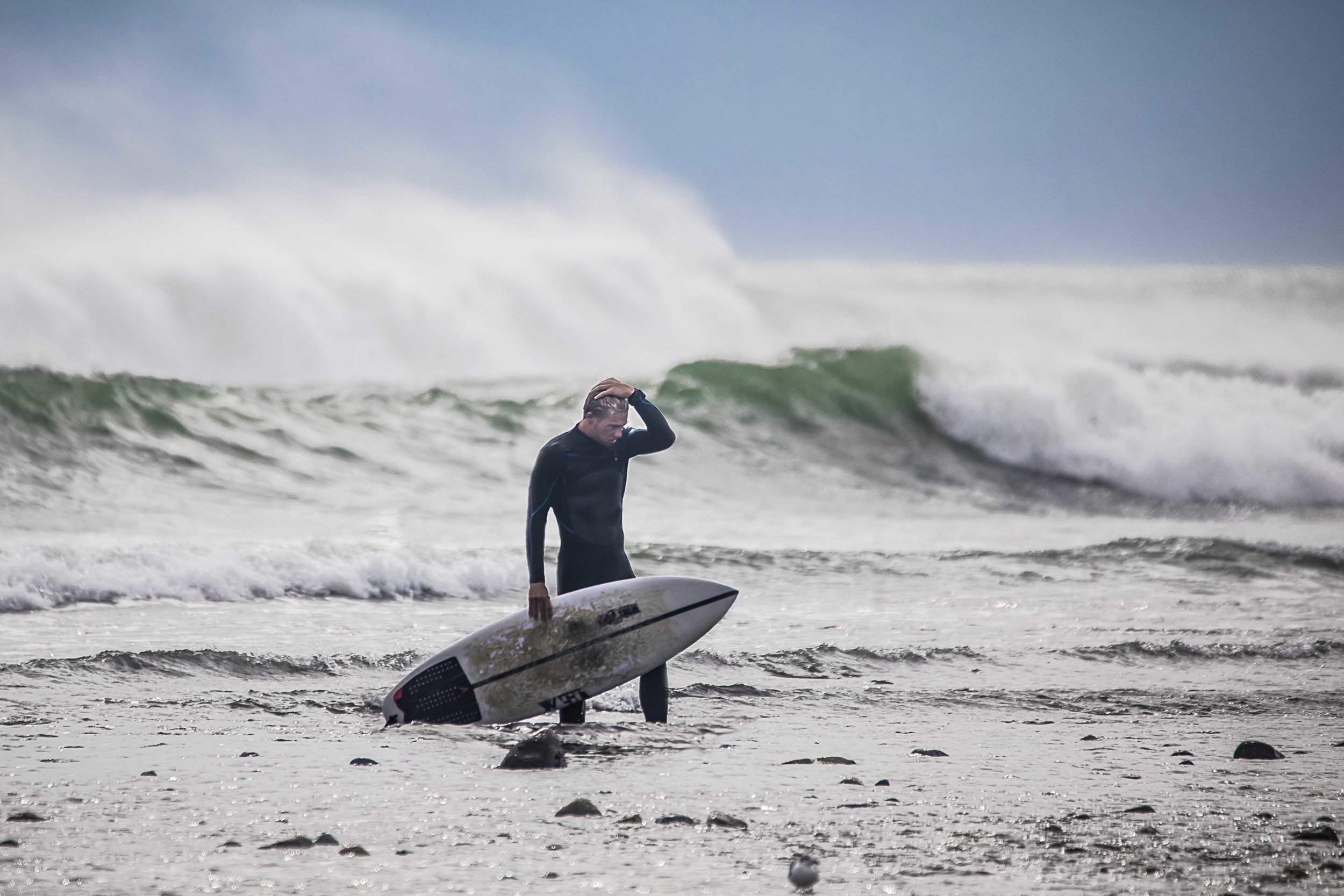 A surfer exits the water after an epic shred session during September's memorable storm surge at Deep Hole in Matunuck, R.I.