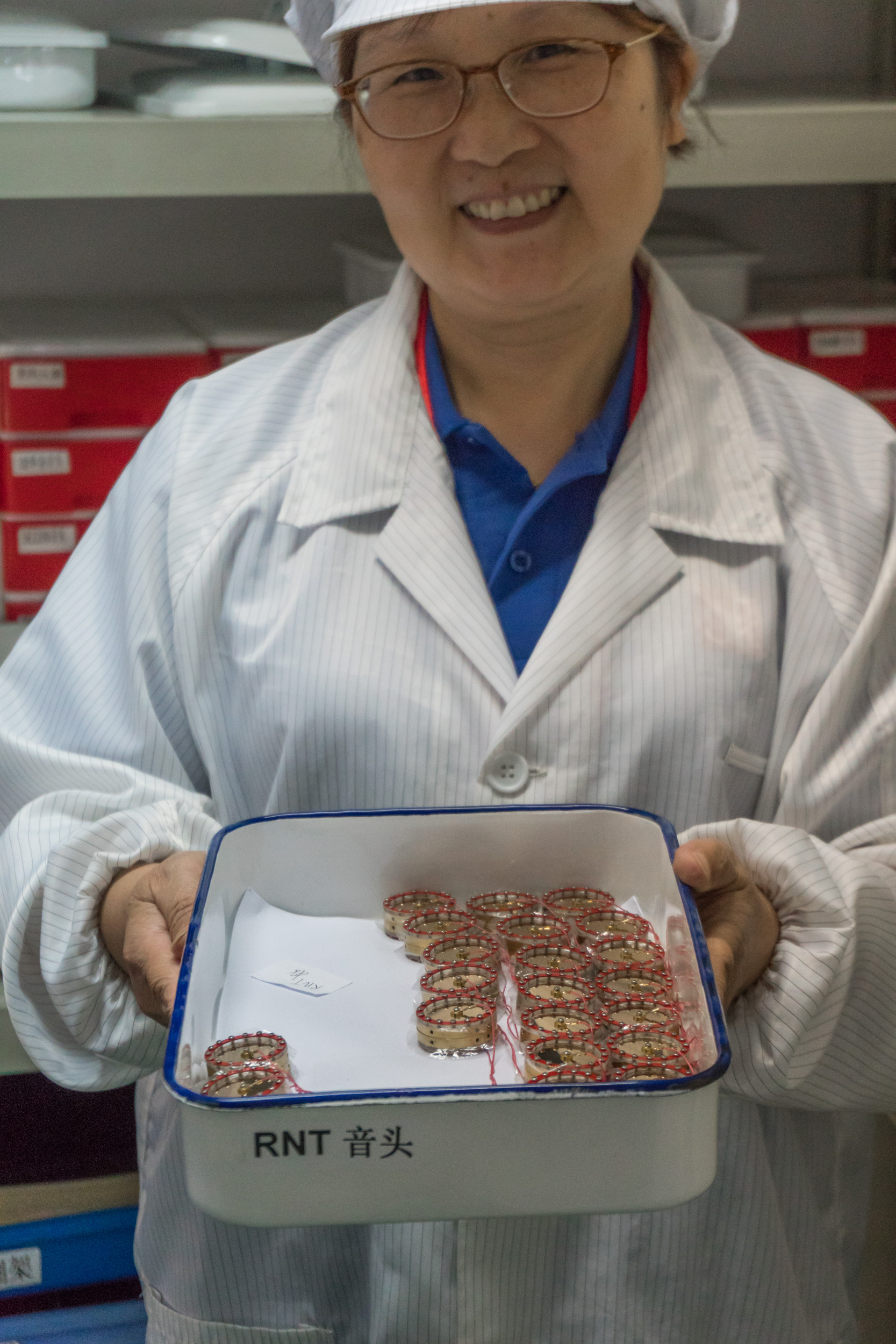 sE's Capsule Master Hongzu Xu holding a tray of RNT capsules, hand-made in our own capsule room.