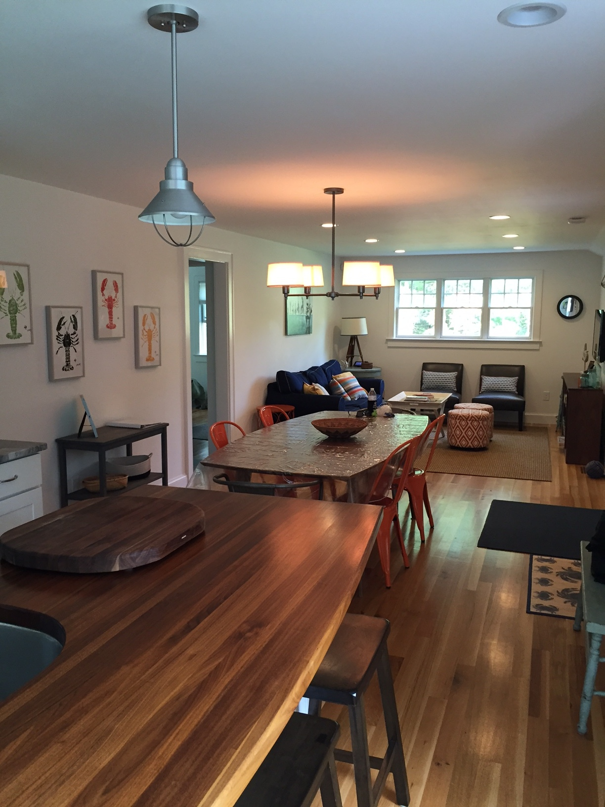 The kitchen, dining and living was open concept. I love the mix of materials and pops of color throughout, especially the  orange Marais chairs  at the dining room table. The  lobster prints  on the wall are from a local artist named John Doherty out of Harwich, MA.