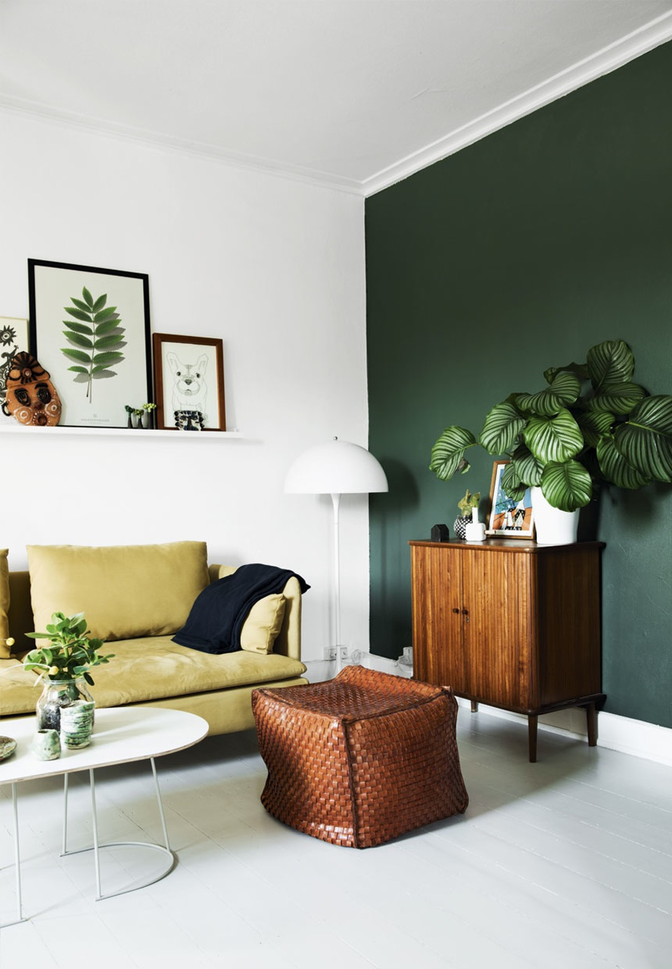 This accent wall is in between an emerald and hunter green, but I love how bold it looks with the citron colored sofa and wooden console table.  Image via  Bolig Magazine .