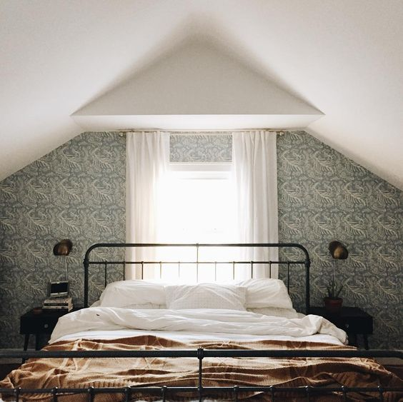 How moody is this bedroom? I love the wallpapered accent wall and how they used sconces vs. table lamps to not overwhelm the area around the bed.  Image via  A Joyful Journey