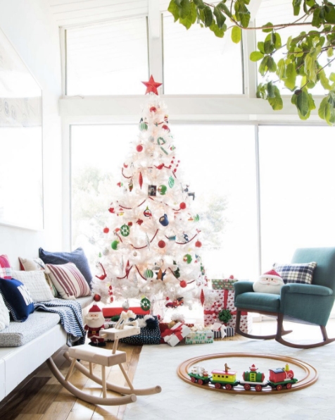 I love the white tree with the more classic colors of Christmas - red and green.   It looks great in this sun filled room.  Image via  Domino  and  Em Henderson