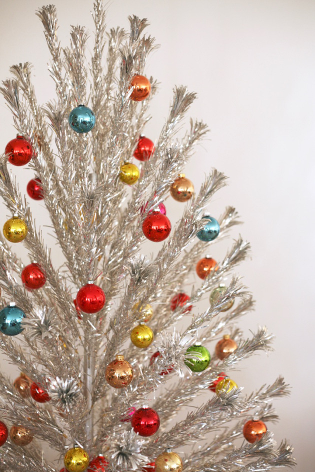 And last but not least, the aluminum Christmas tree!  I picked up one of these a few years ago at an antique market.  They are super fun to decorate with bright glass ornaments like the one pictured here. And fortunately they don't need lights since they are sparkly on their own (but you can't use them anyway since it's a fire hazard).  Image via  Suburban Pop