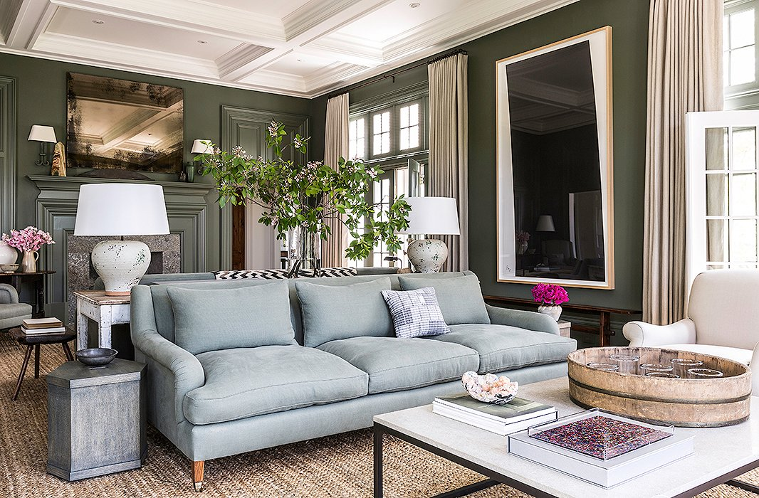 This beautiful sofa provides the icey blue in this Connecticut living room. The olive green walls and natural textures throughout, in particular the sisal rug and cream colored drapes, warm up the space, making it the perfect place to curl up with a cup of tea and a good book.  Image: Lesley Unruh via  One Kings Lane