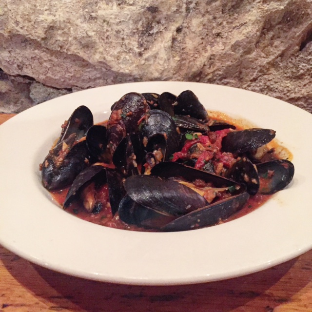 Mussels in a spicy red sauce against the back drop of a cellar wall that housed one of the original Gold Rush Mines.