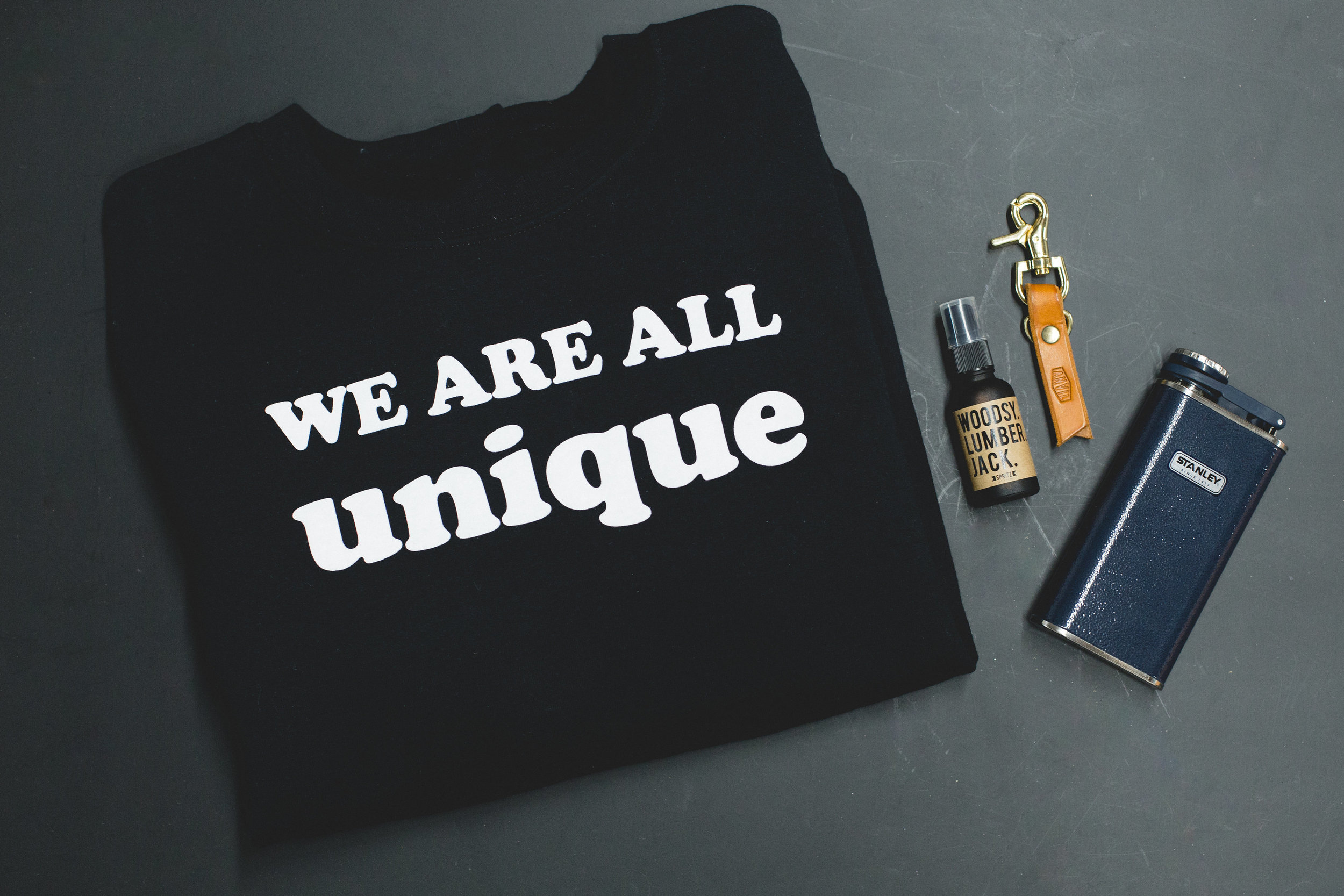 Unique Essentials Kit! - Stay fresh with a cozy Unique sweatshirt and classic STANLEY flask, topped with a leather Anvil keychain and Woodsy Lumberjack spray from Happy Spritz.