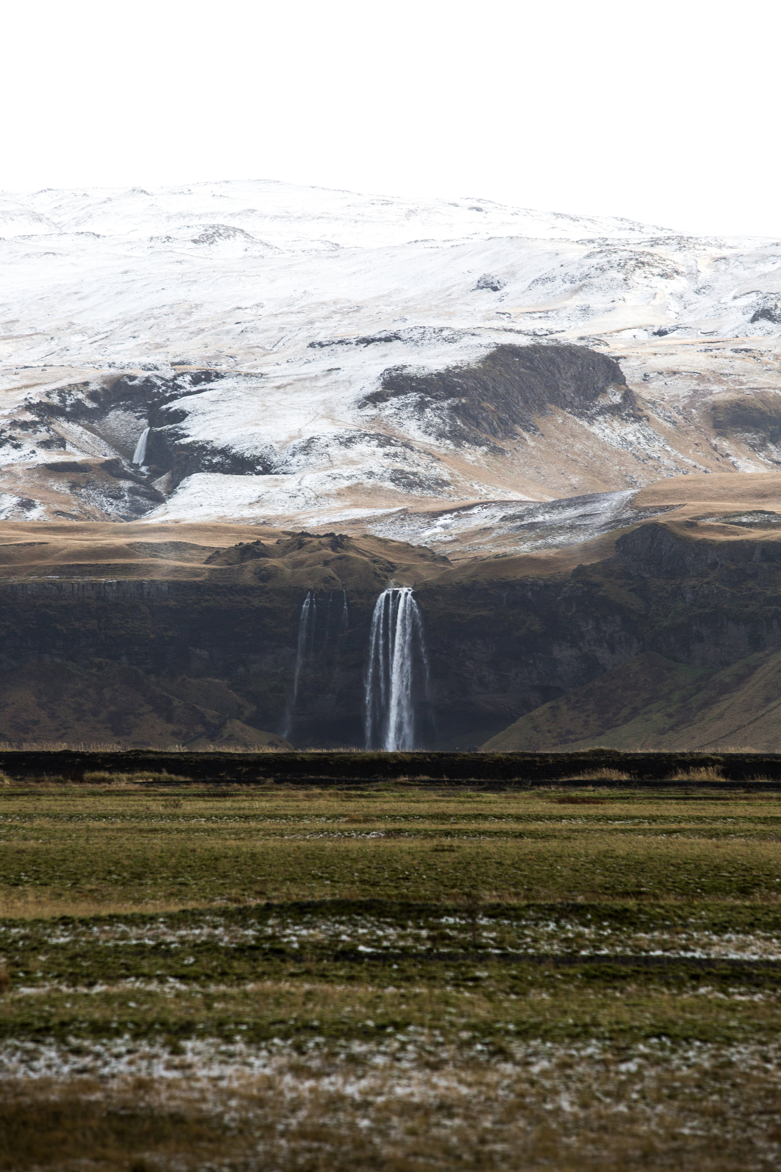 In the distance, Seljalandsfoss spills water from the glacier and rains of the day. Waterfalls are everywhere here, each worth of stopping for admiration. It wasn't quite snow, but bits of hail hit us on and off in the minutes trying to frame a decent photo from afar.